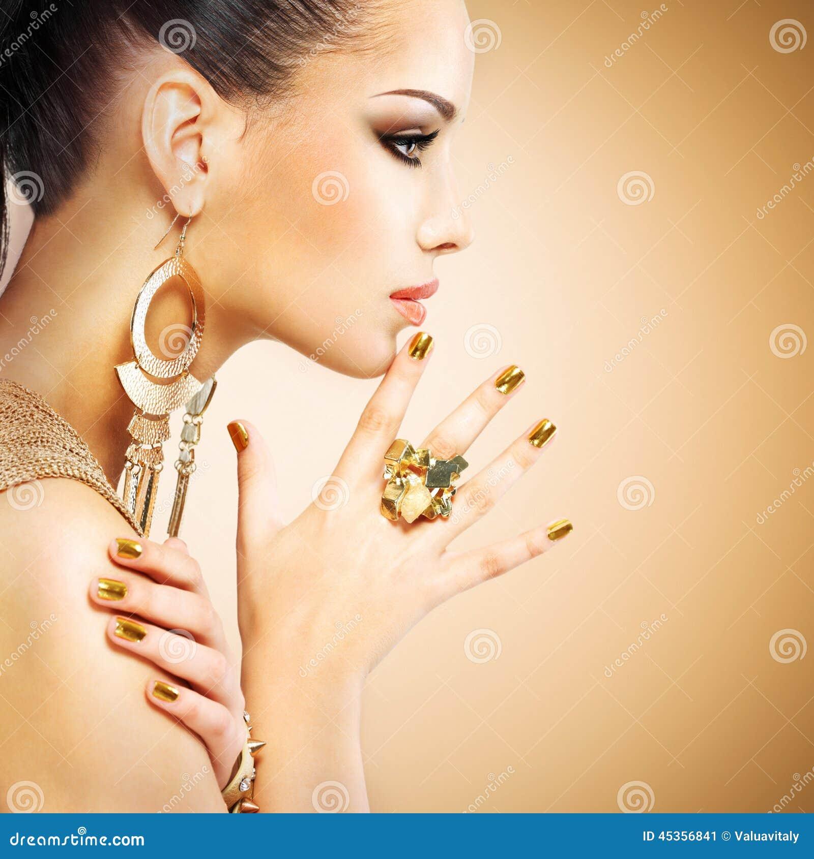 Profili il ritratto della donna di modo con bella mani dorata