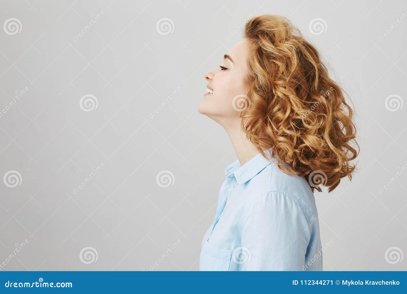 Profili il ritratto di godere della donna felice con brevi capelli ricci, sorridendo largamente, la blusa blu casuale d uso e la