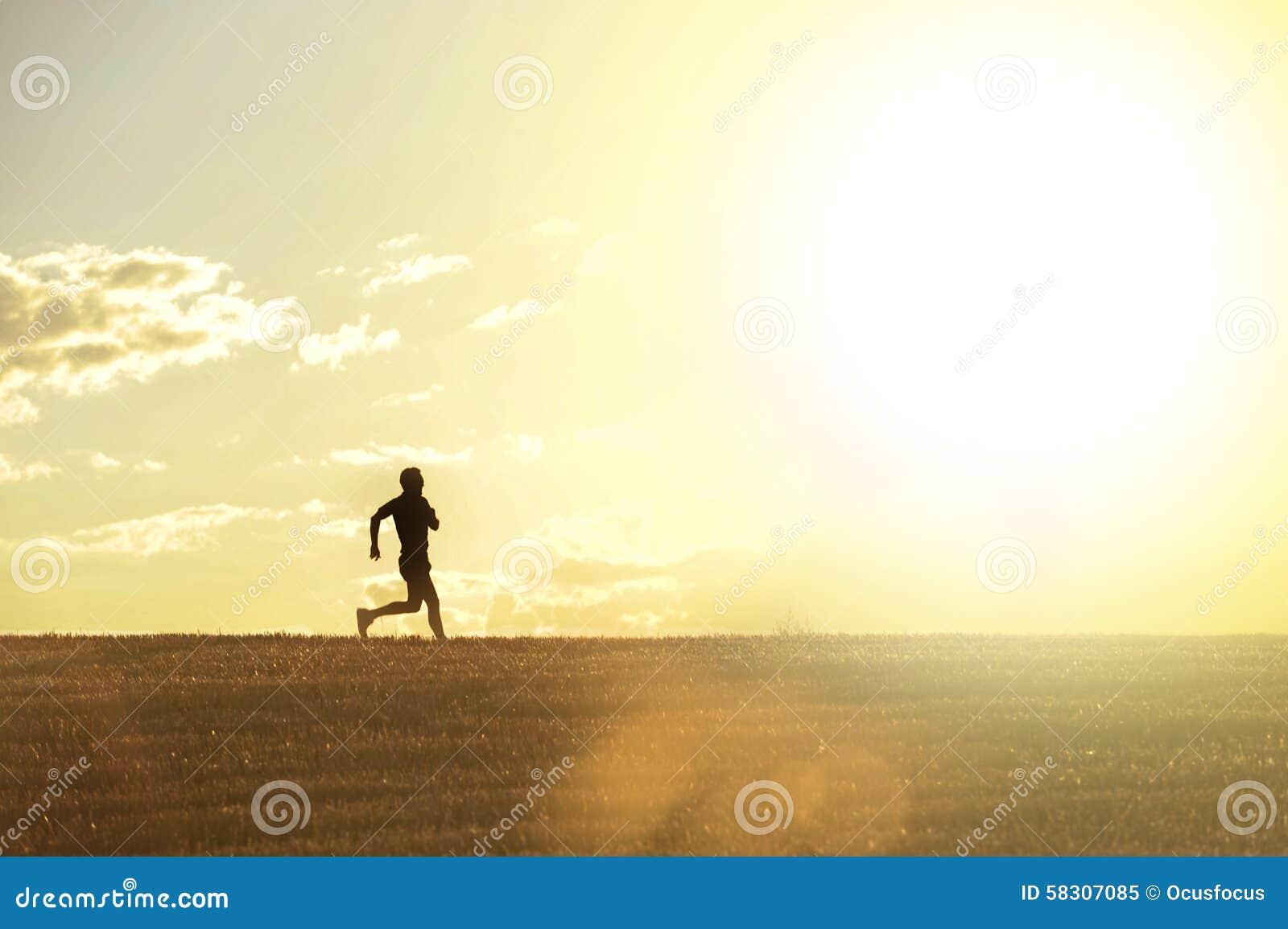 Profilkontur av spring för ung man i bygd som utbildar jogga disciplin för argt land i sommarsolnedgång