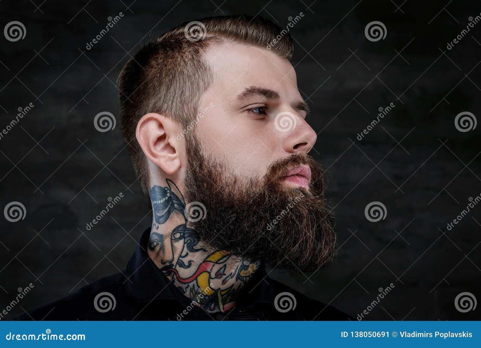 Profilowy portret ekspresyjny brodaty mężczyzna z tatuażami na jego szyi na ciemnym tle,