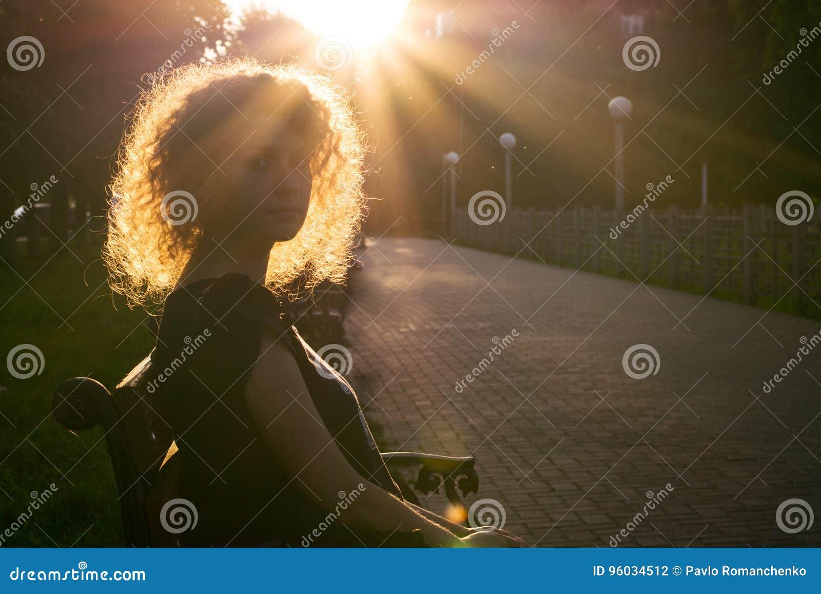 Profilowy portret kędzierzawa dziewczyna przeciw złotemu słońce racy w sumie