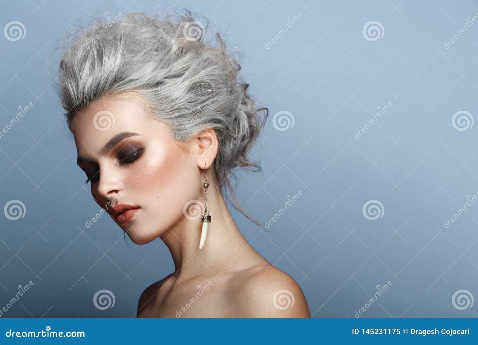 Profilowy portret modna, wspaniała młoda blondynki kobieta, uzupełnia, nadzy ramiona na błękitnym tle,
