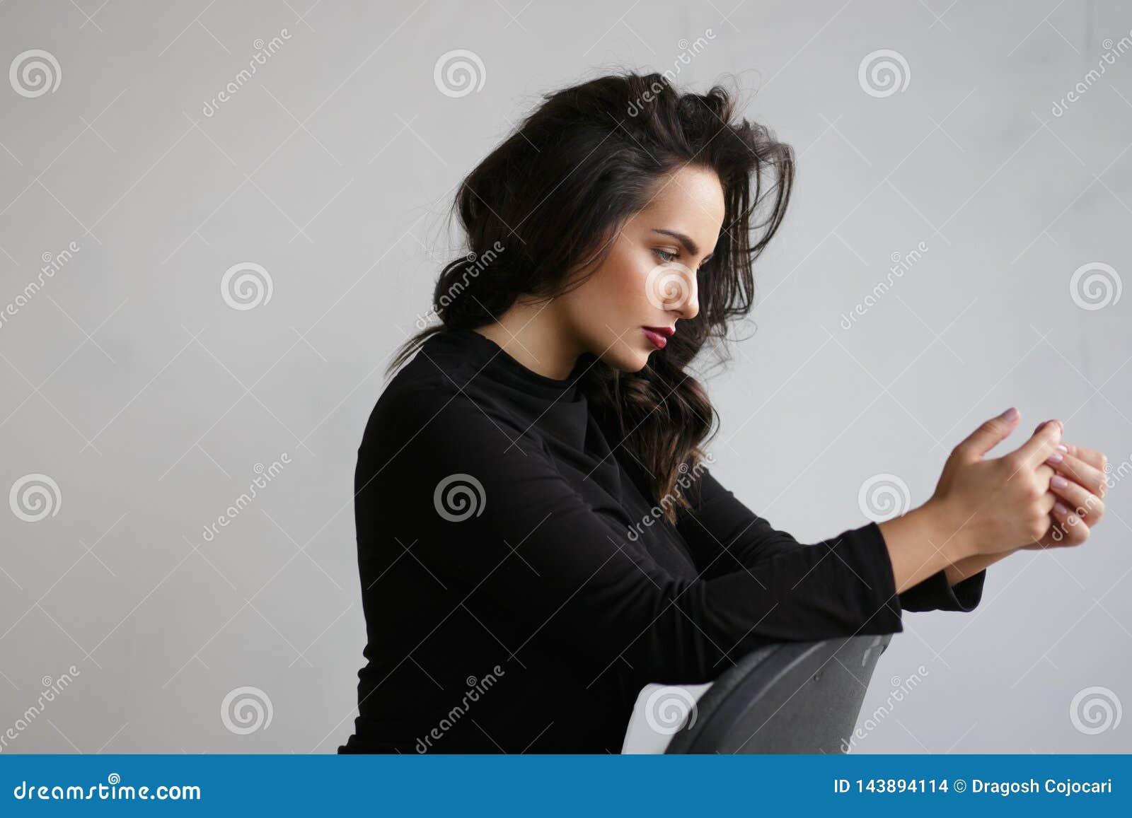 Profilowy portret piękna zadumana kobieta w czerni sadzającym na krześle w studiu, na popielatym tle