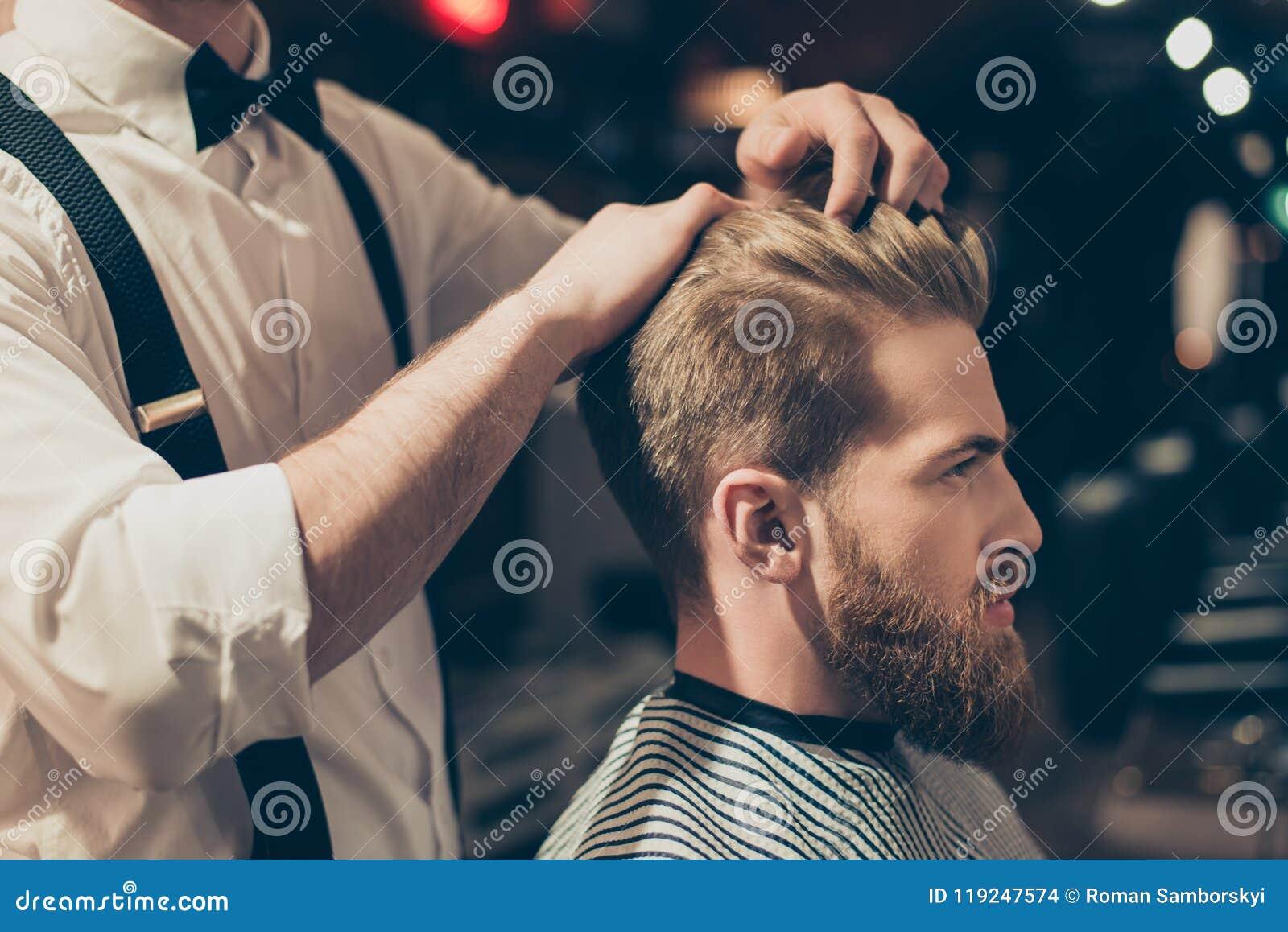 Profilowy strony zakończenie w górę widoku portreta przystojny virile macho mężczyzna ma jego włosy ciącego w zakładzie fryzjersk