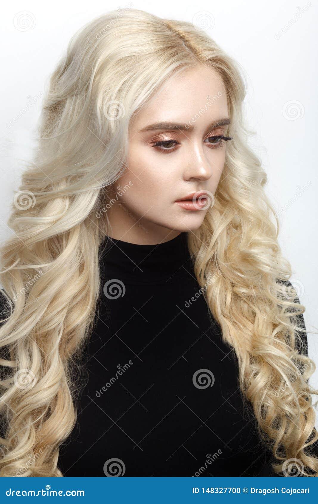 Profilståenden av en kvinna med den lockiga blonda frisyren i svart förkläde som är mjuk utgör, isolerat på en vit bakgrund