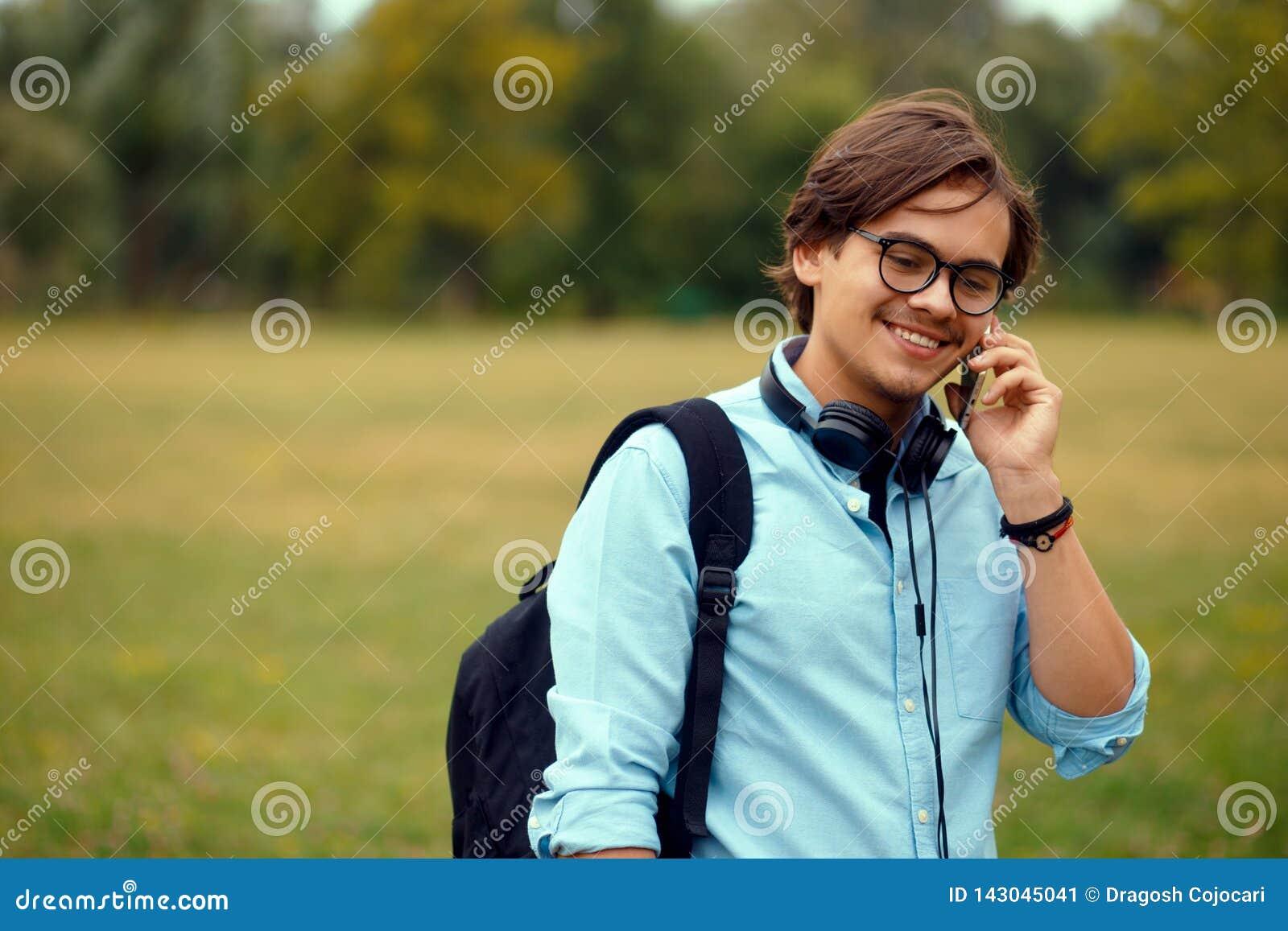 Profilståenden av en ung smiligstudent som talar på smartphonen, på en allmänhet, parkerar bakgrund, med kopieringsutrymme