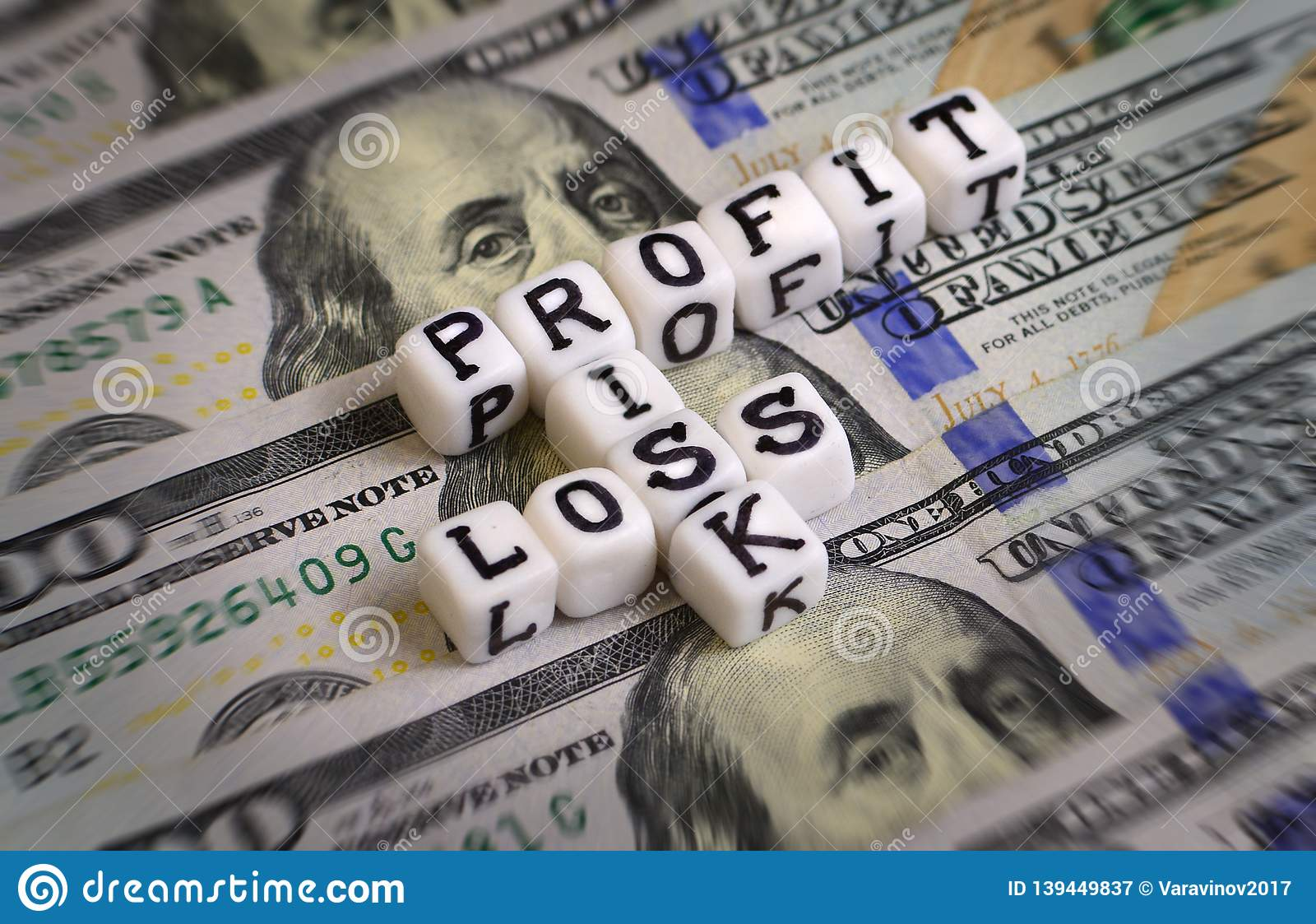 Profit or Loss, or Risk concept with letter cubes on a dollar bank notes.