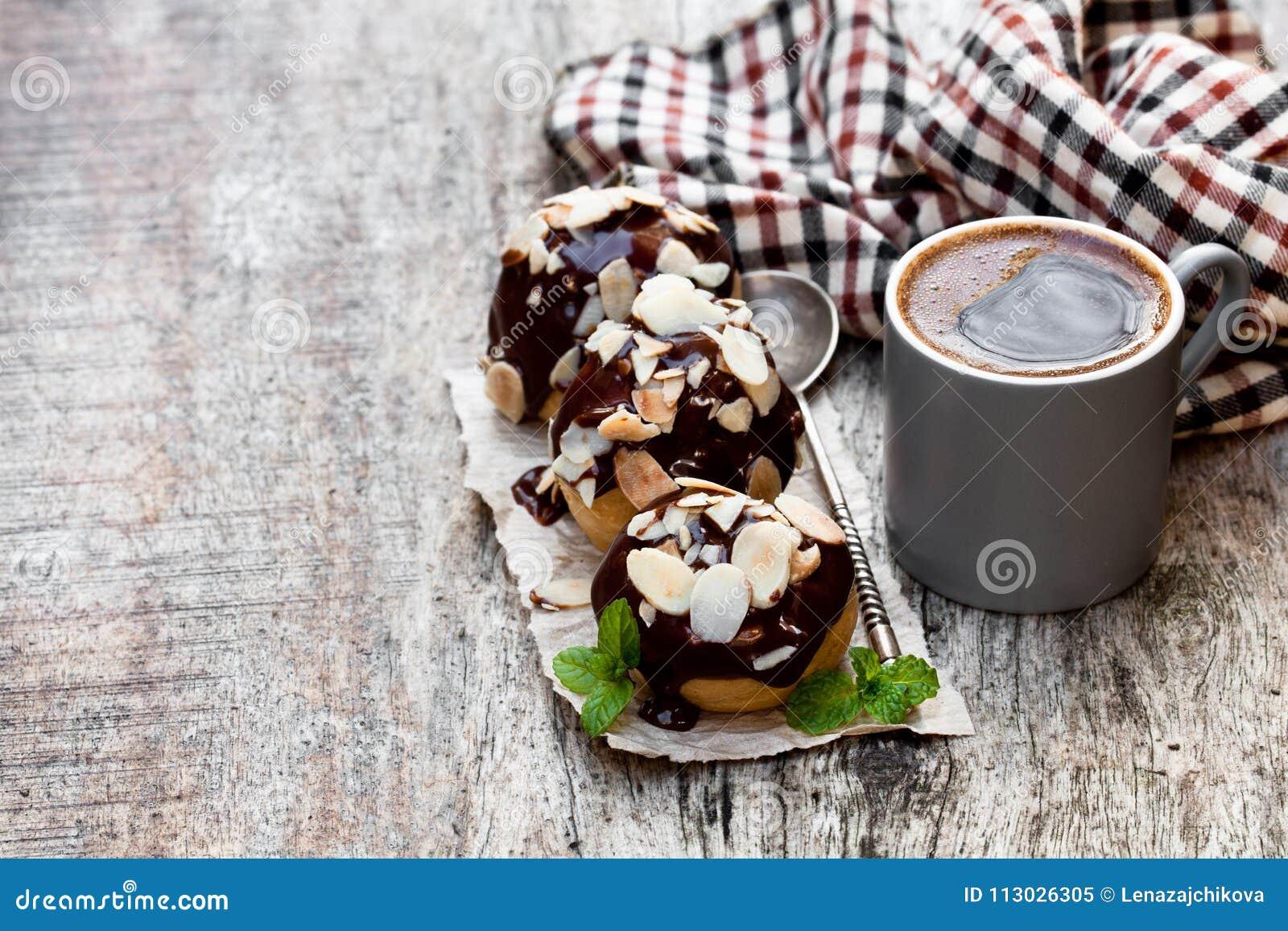 Profiteroles hechos en casa con las almendras y la taza de café en de madera