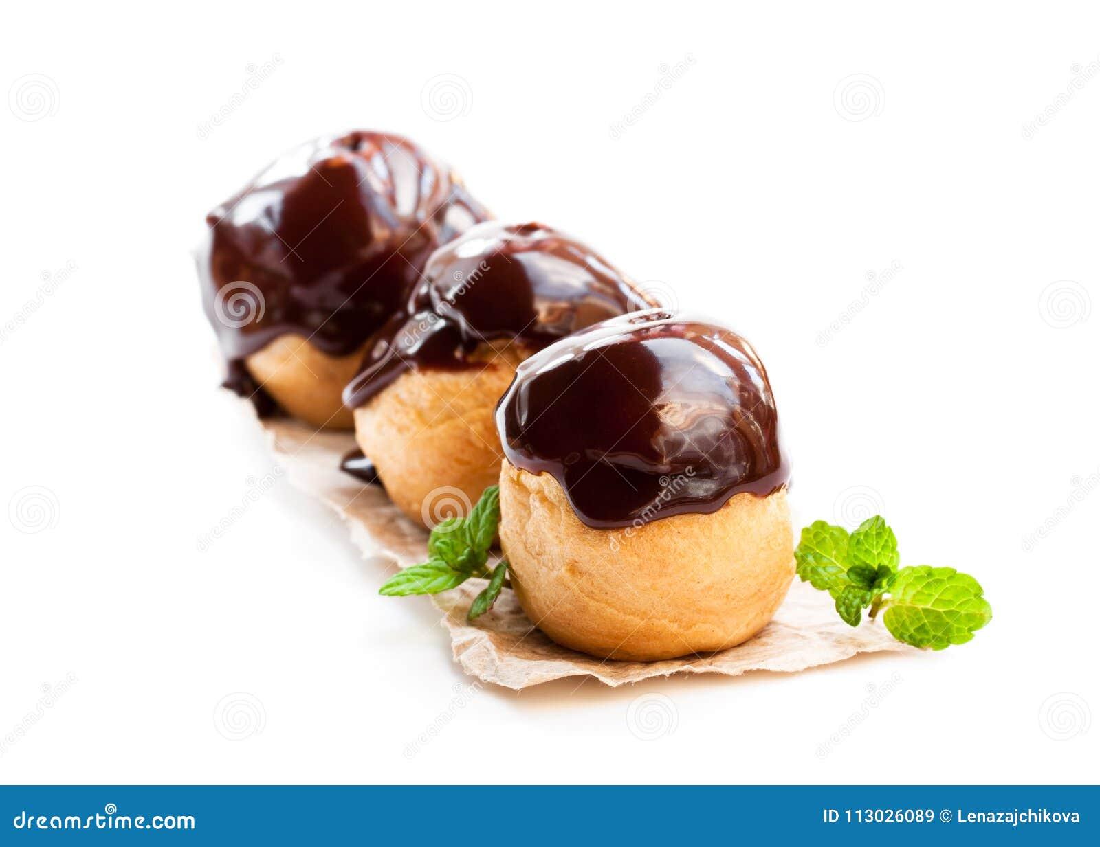 Profiteroles hechos en casa del chocolate aislados en blanco
