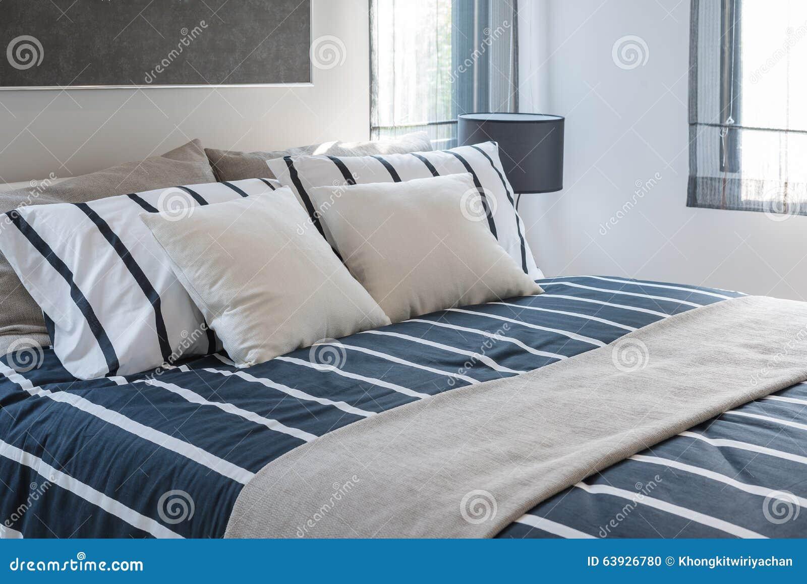 Progettazione moderna della camera da letto con i cuscini sul letto blu fotografia stock - Letto con cuscini ...