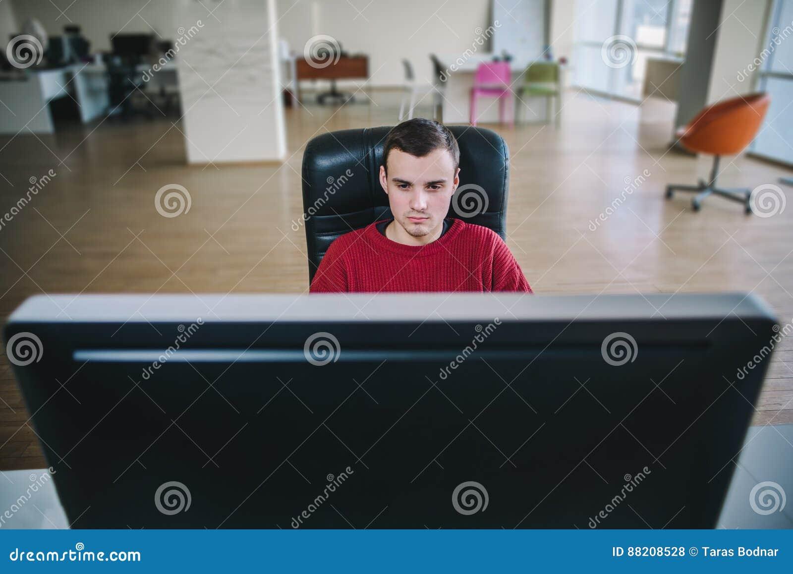 Programador hermoso joven del inconformista que se sienta en un monitor de computadora y un trabajo grandes Oficina del flujo de