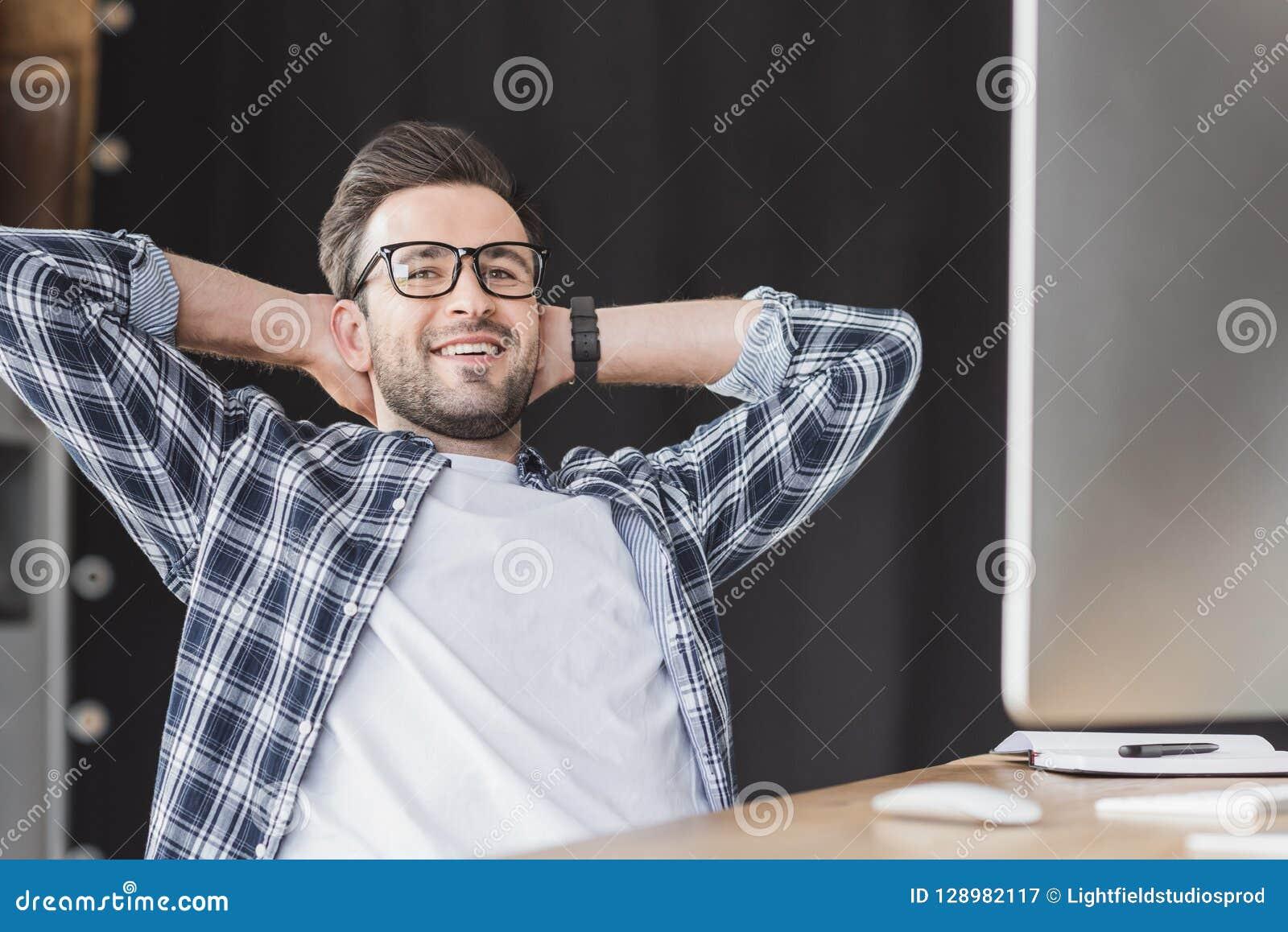 Programador joven hermoso en lentes que sonríe en la cámara mientras que se sienta con las manos detrás de la cabeza