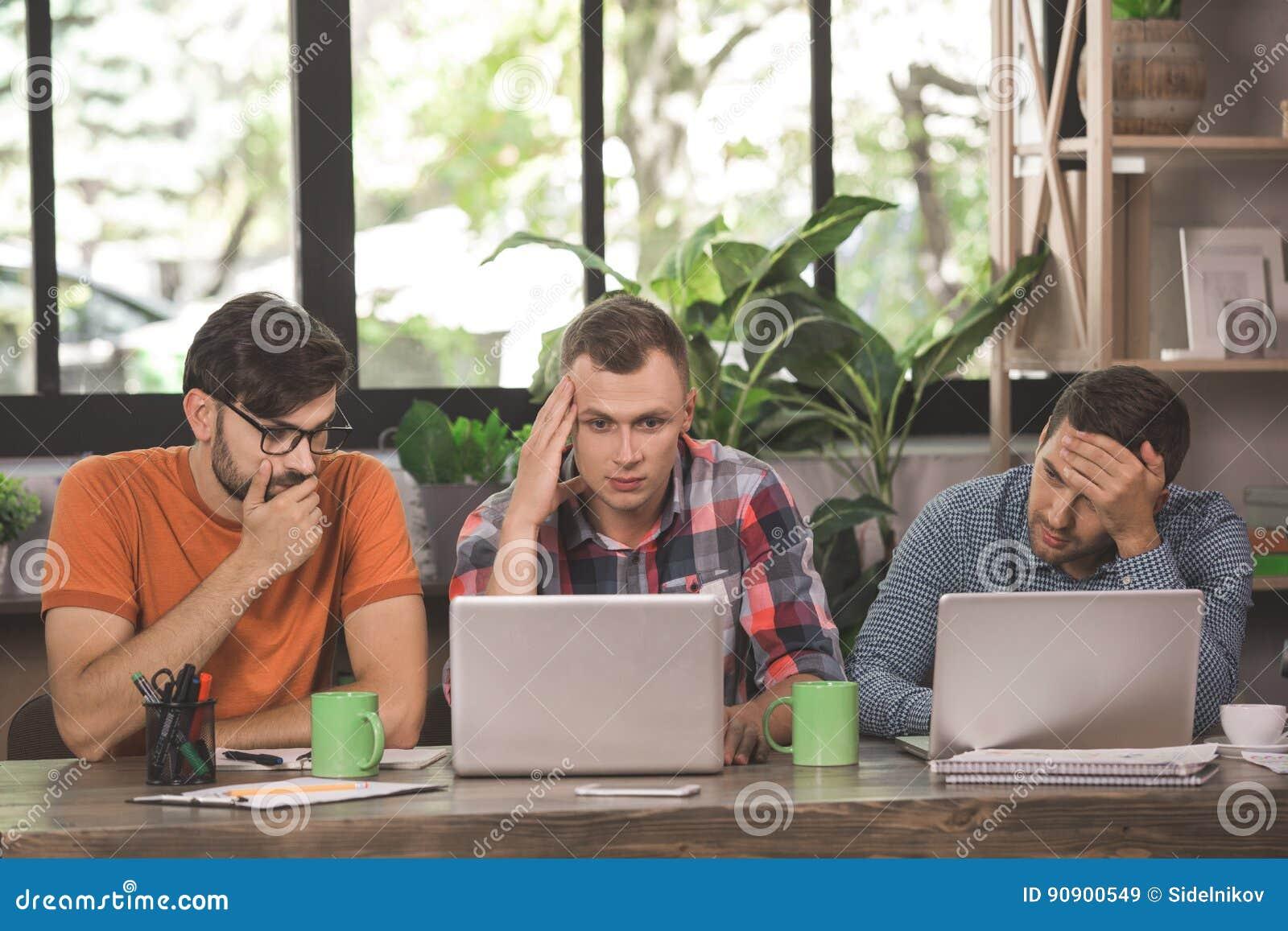 Programadores de los hombres jovenes que trabajan junto en la oficina