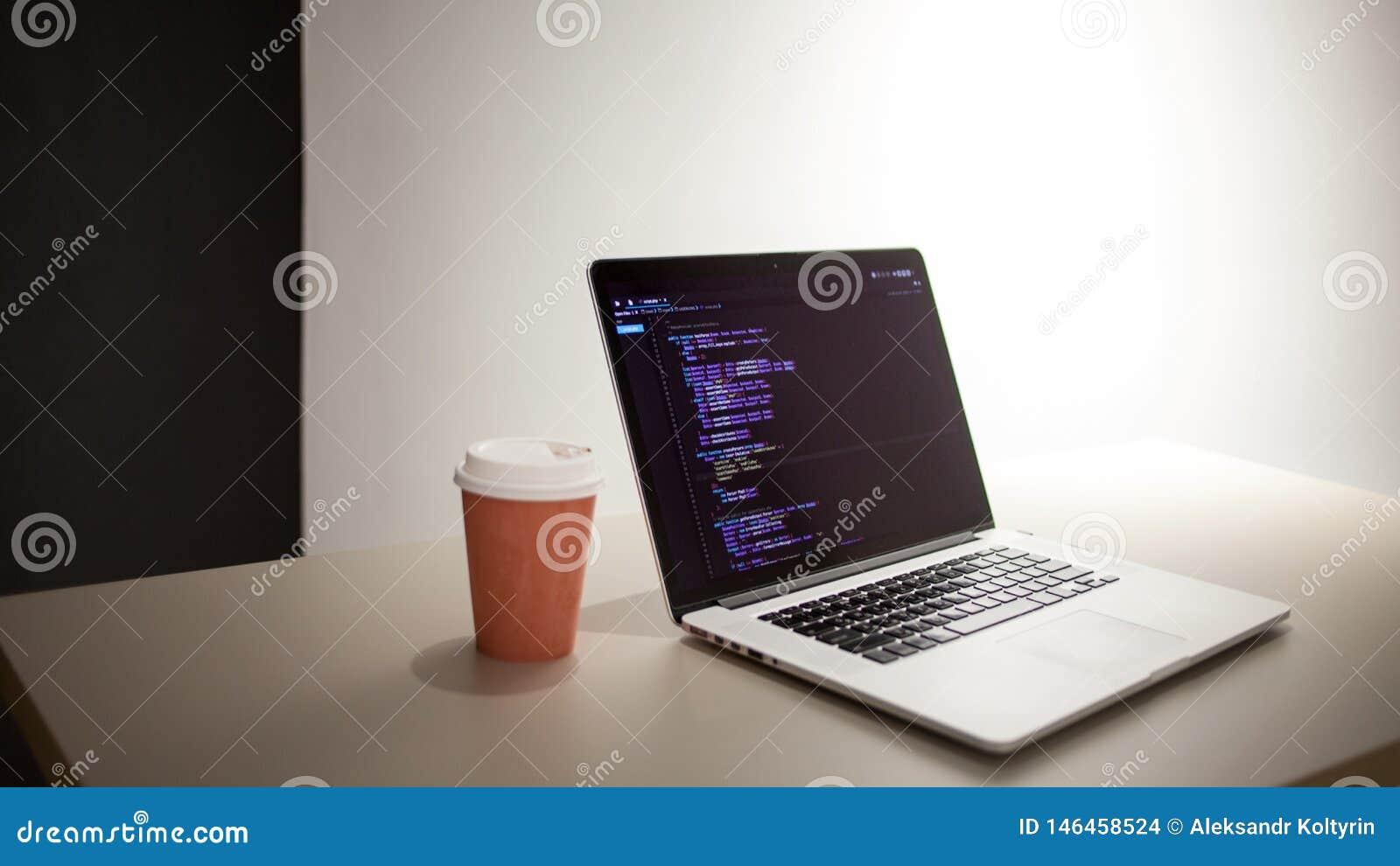 Programmerares arbetsplats, b?rbar dator med projektkod Utveckling av websites och applikationer