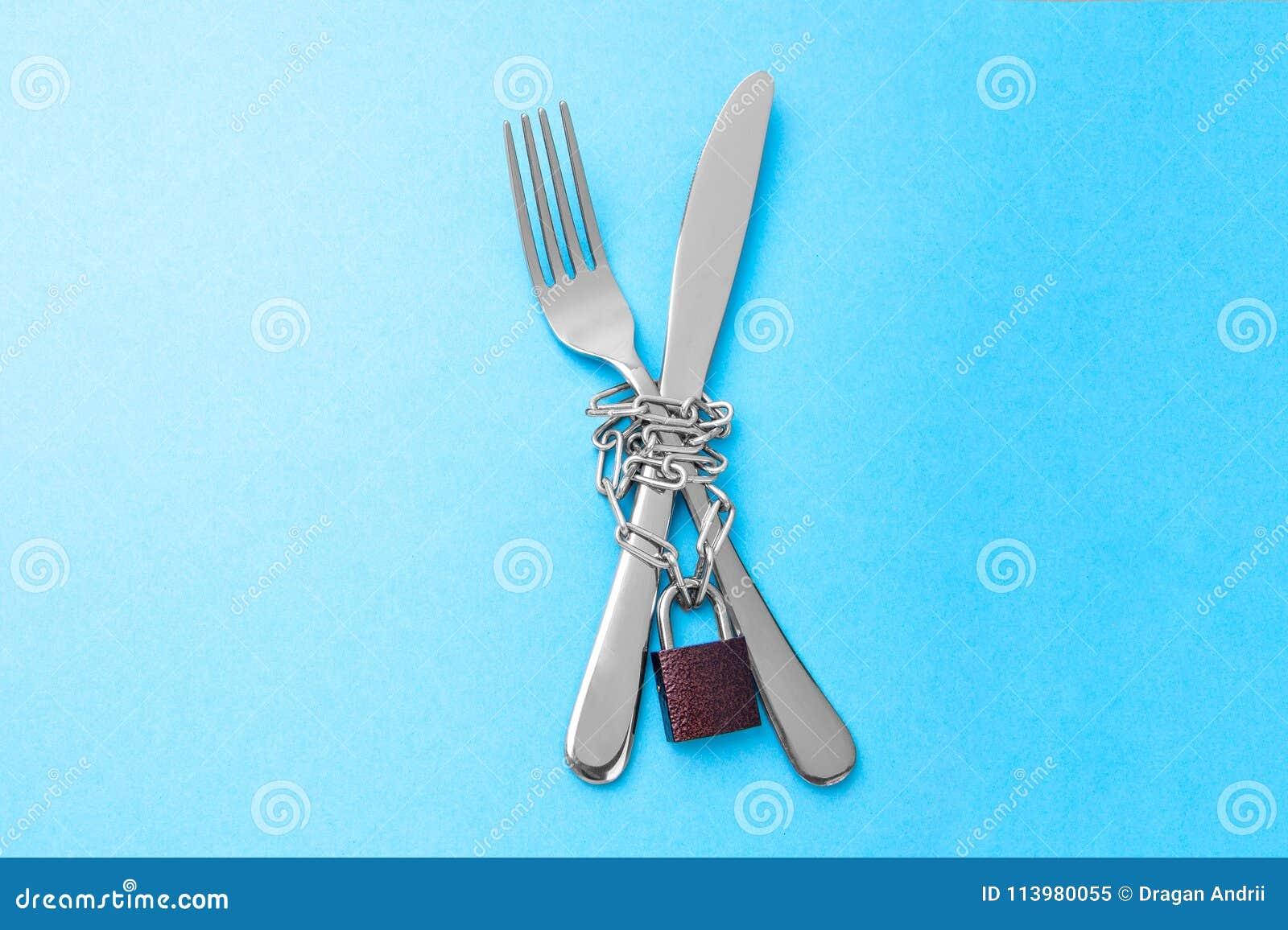 Prohibición en la comida como dieta para la pérdida de peso La bifurcación y el cuchillo se envuelven en una cadena y se cierran
