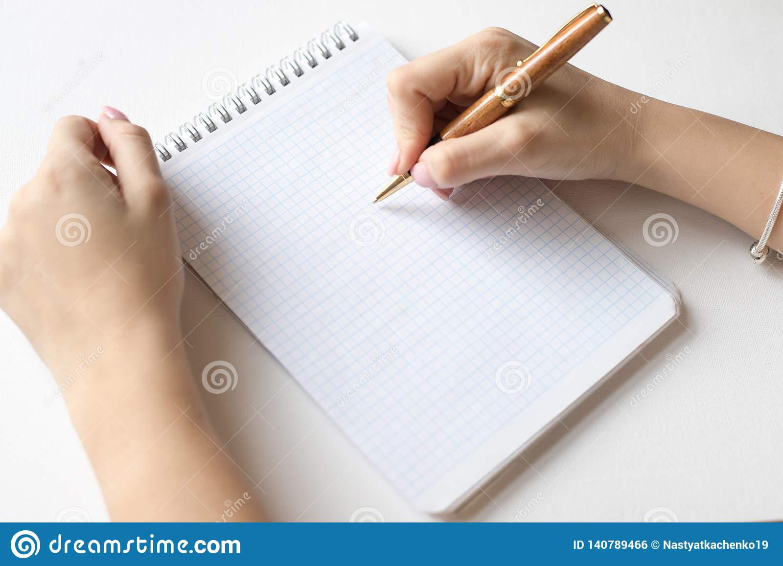 Projekta pojęcie - Odgórny widok ślimakowaty notatnik, biała strona i pióro, kobieta chwyta pióro odizolowywający na białym tle d