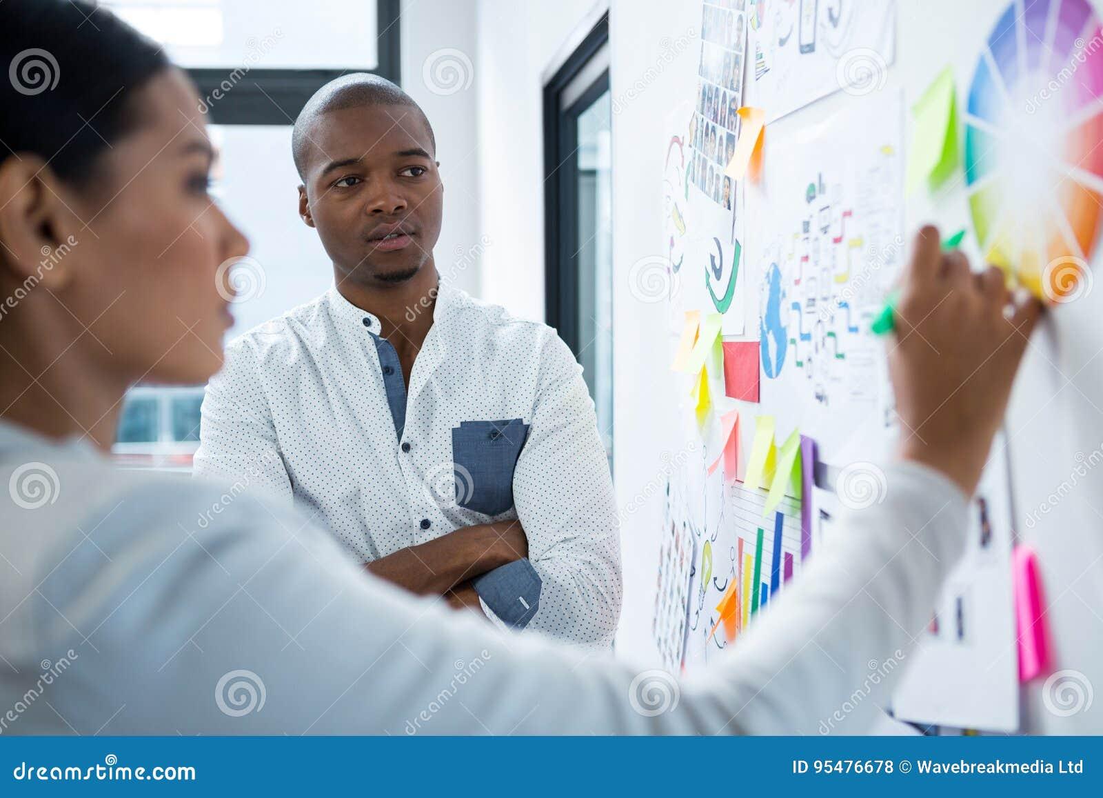 Projektant grafik komputerowych dyskutuje nad mapami i wykresem