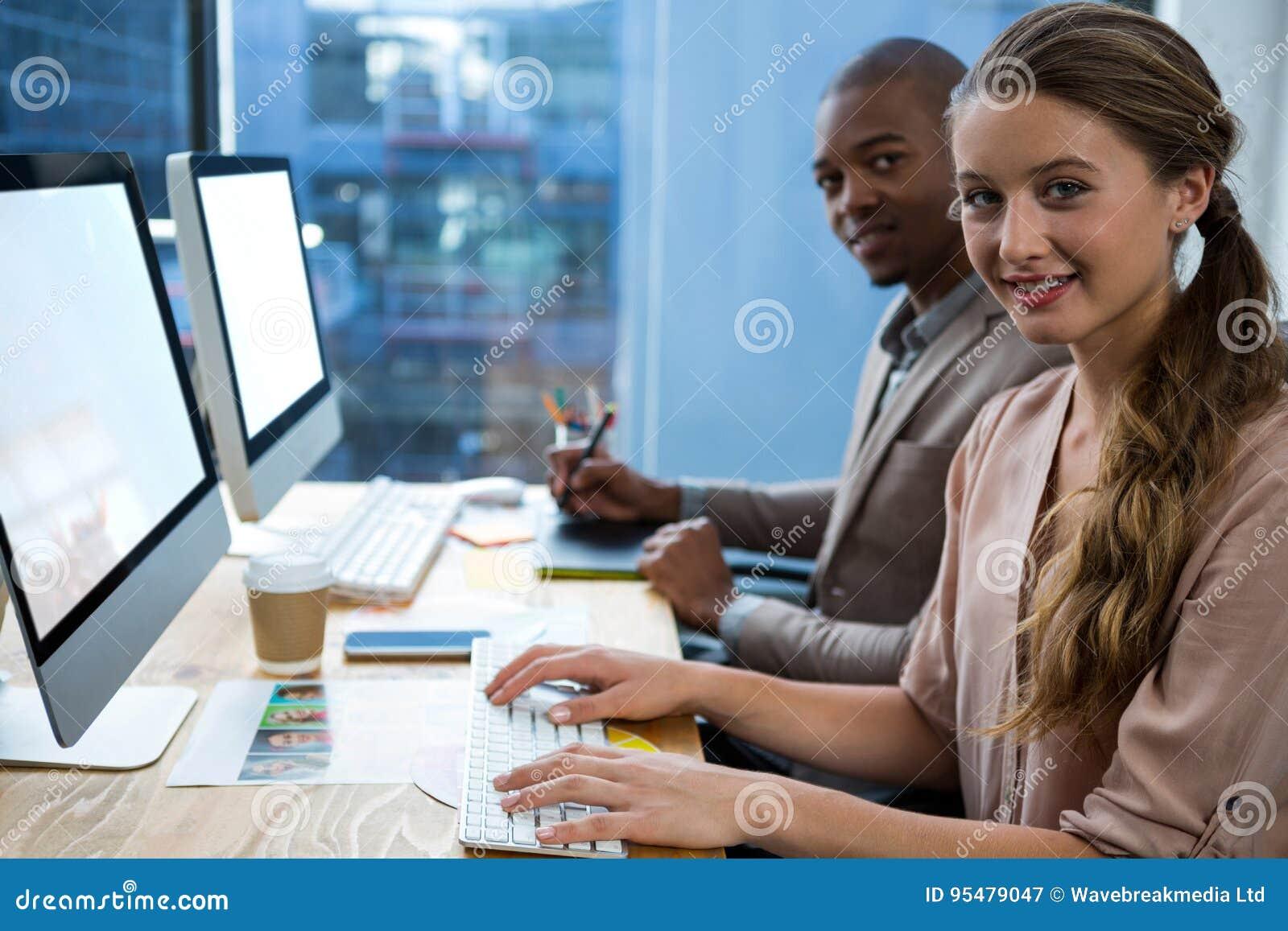 Projektant grafik komputerowych pracuje przy biurkiem z kolegą