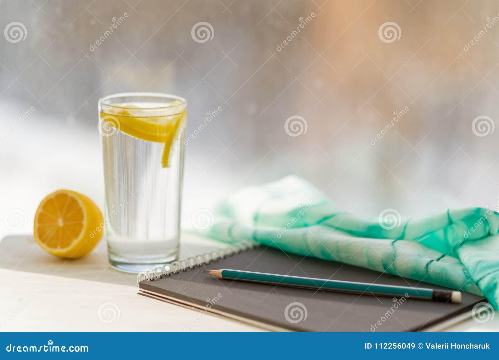 Projektanta czarny notatnik, szkło woda mineralna z cytryną, nadokienny tło
