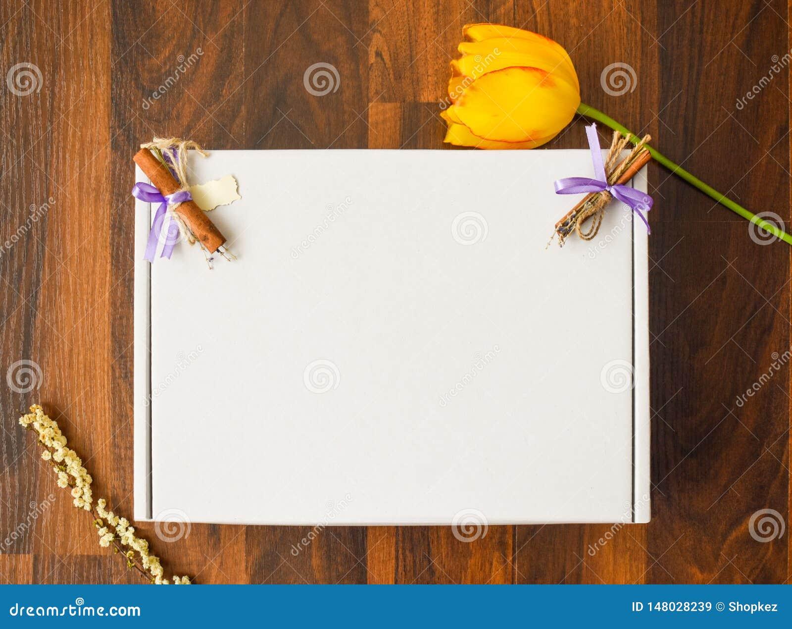 Projektuj?ca Akcyjnego fotografii mockup cyfrowa kartoteka pusty kartonu kwadrat z drewnianym podłogowym tłem z żółtym tulipanem,