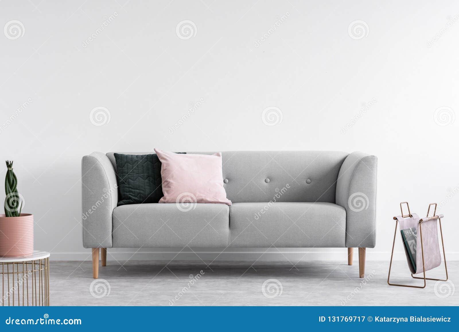 Projeto mínimo escandinavo com sofá cinzento, foto real com espaço da cópia na parede