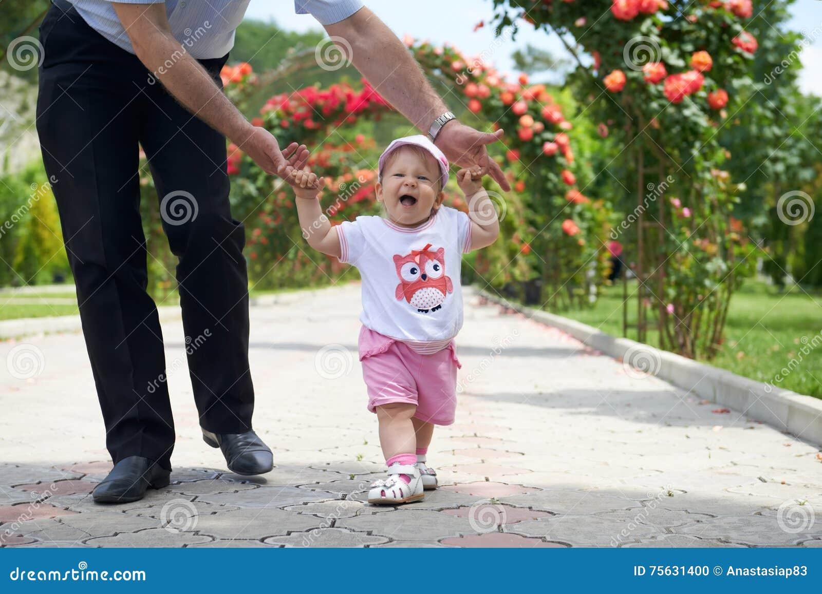 Promenade d été Premières étapes de Childs dans les mains fortes de pères