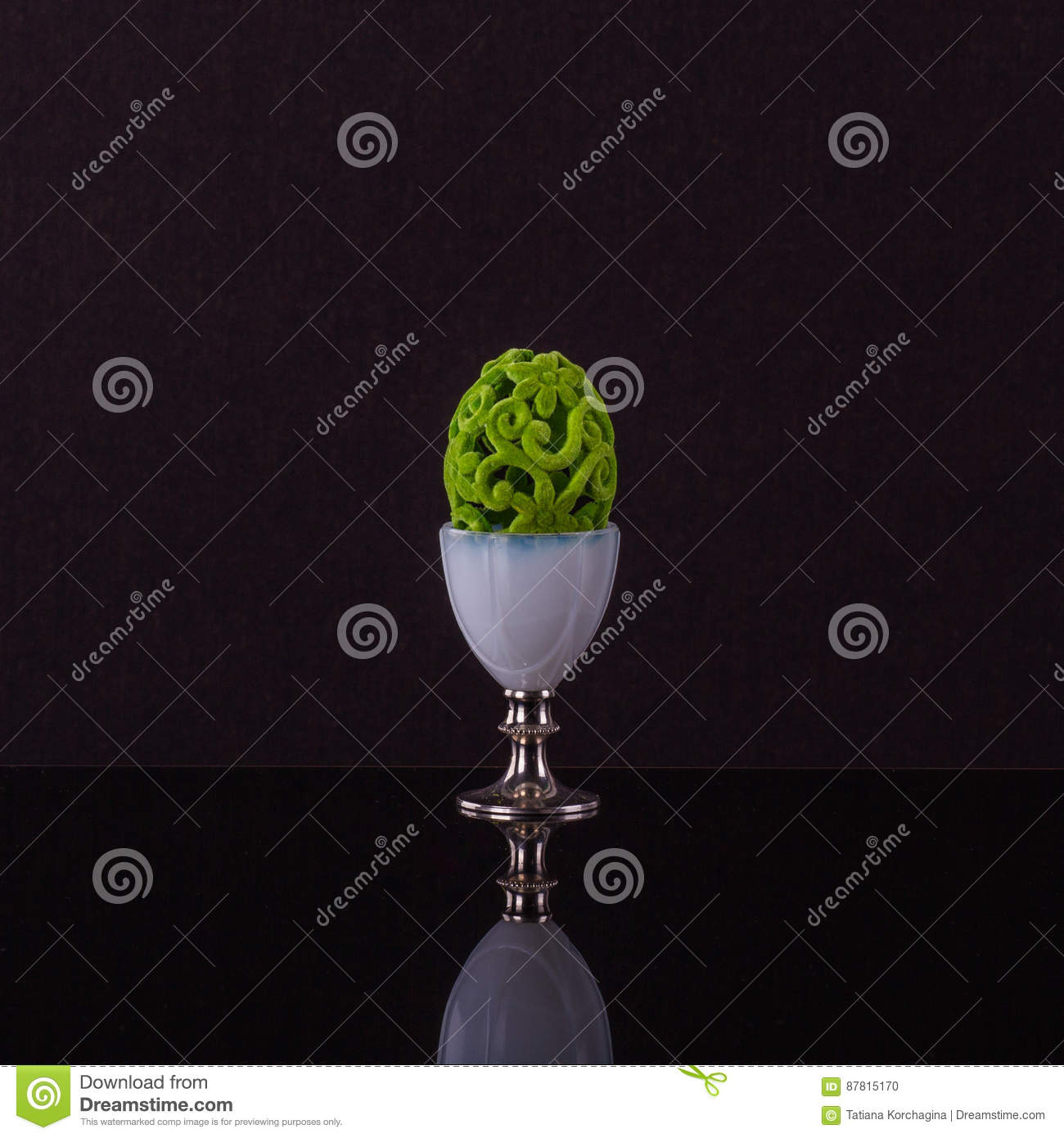 Prominent egg cup with elegante posh green Easter egg