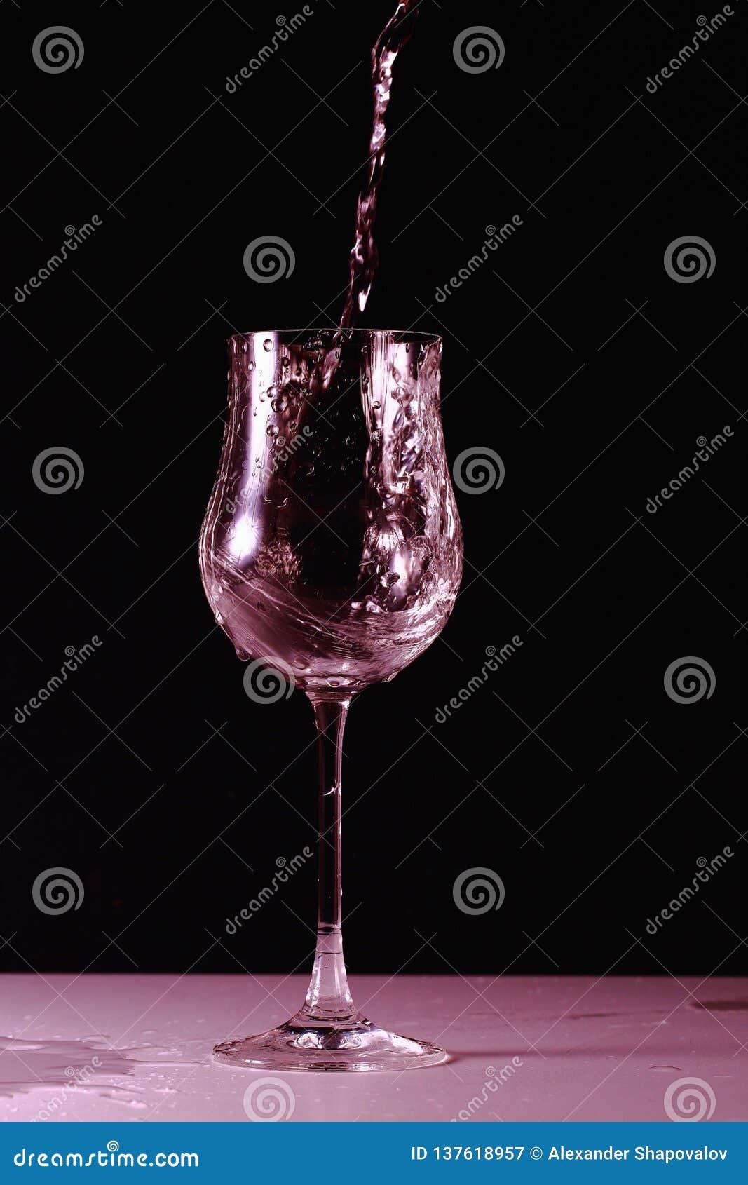 Propósito ascendente cercano de salpicar el agua en el vidrio aislado en rosa Fondos hermosos