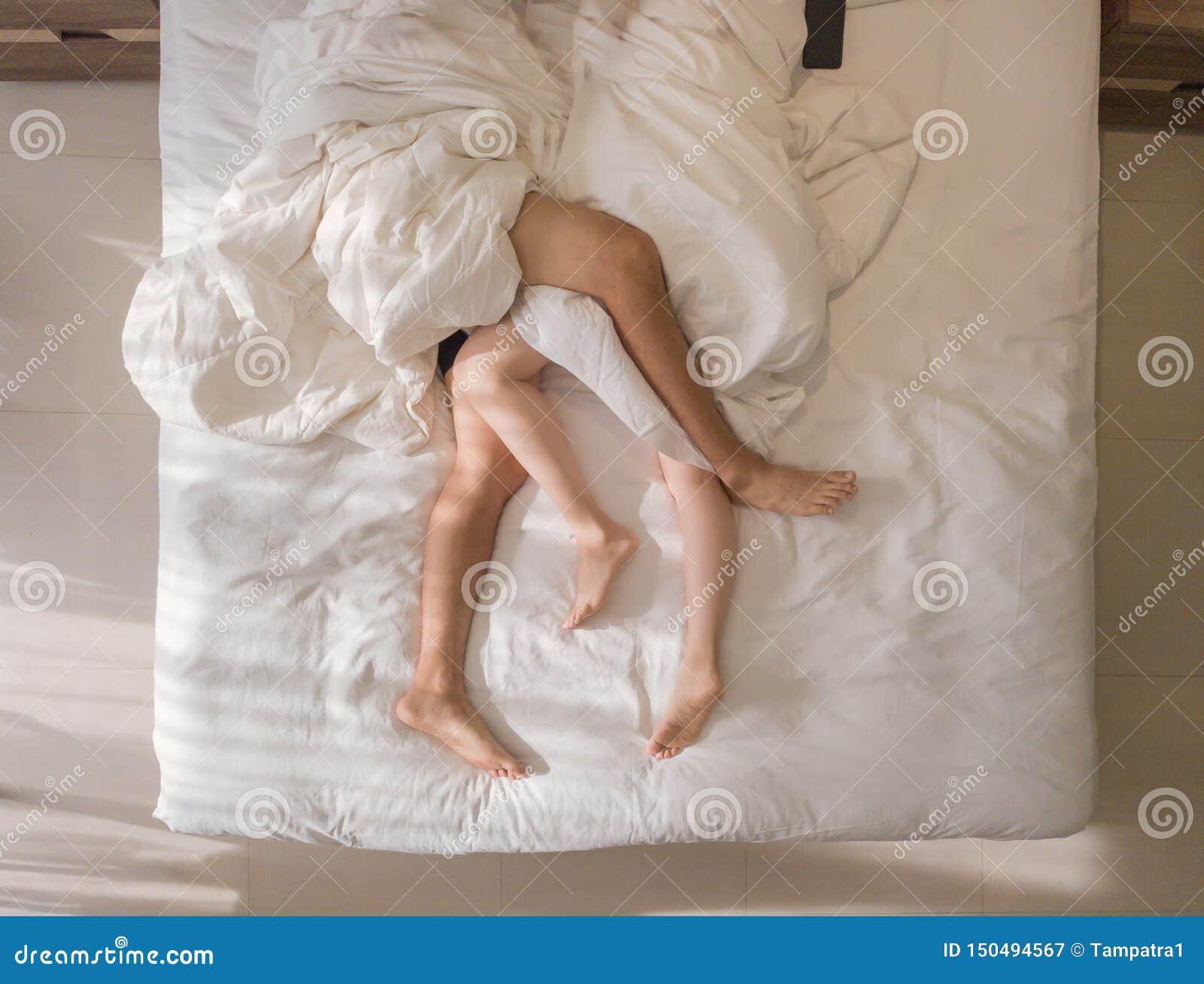 Propósito superior de dormir romántico de los pares pies desnudos de sus piernas que mienten en una cama con la manta blanca en c