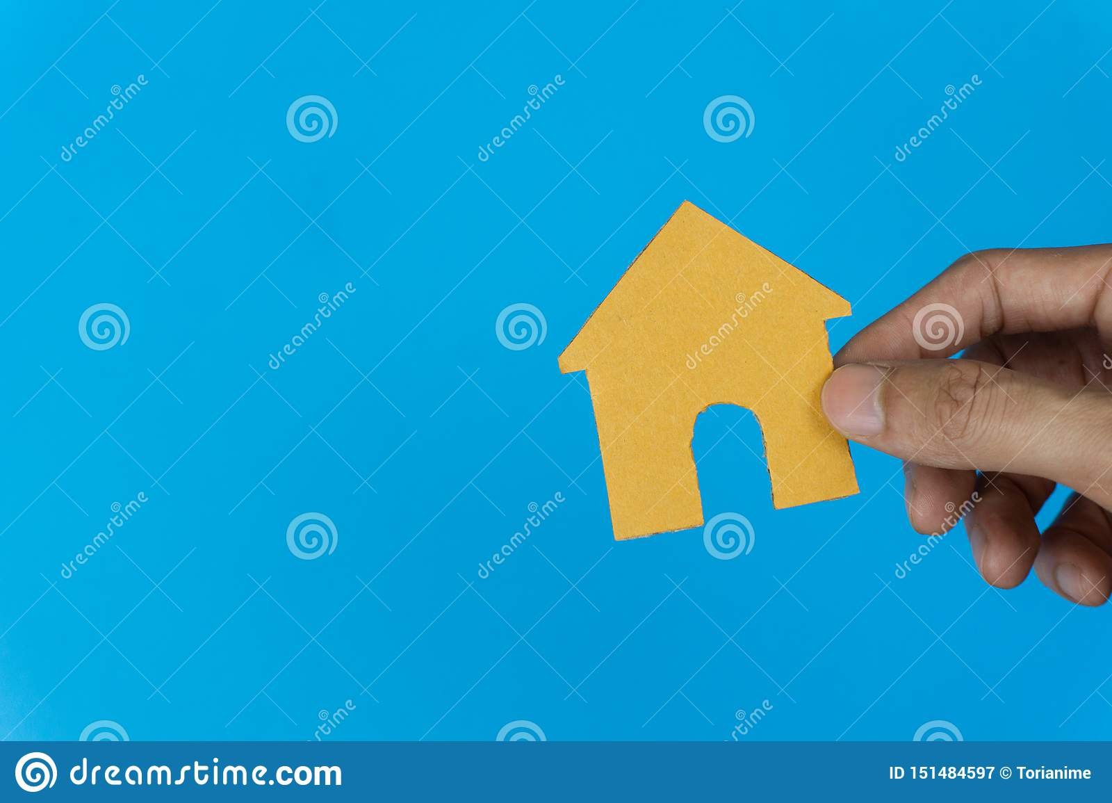 Property concept. Home loan, reverse mortgage, housing, business and finance. A man hand holding small house on blue background