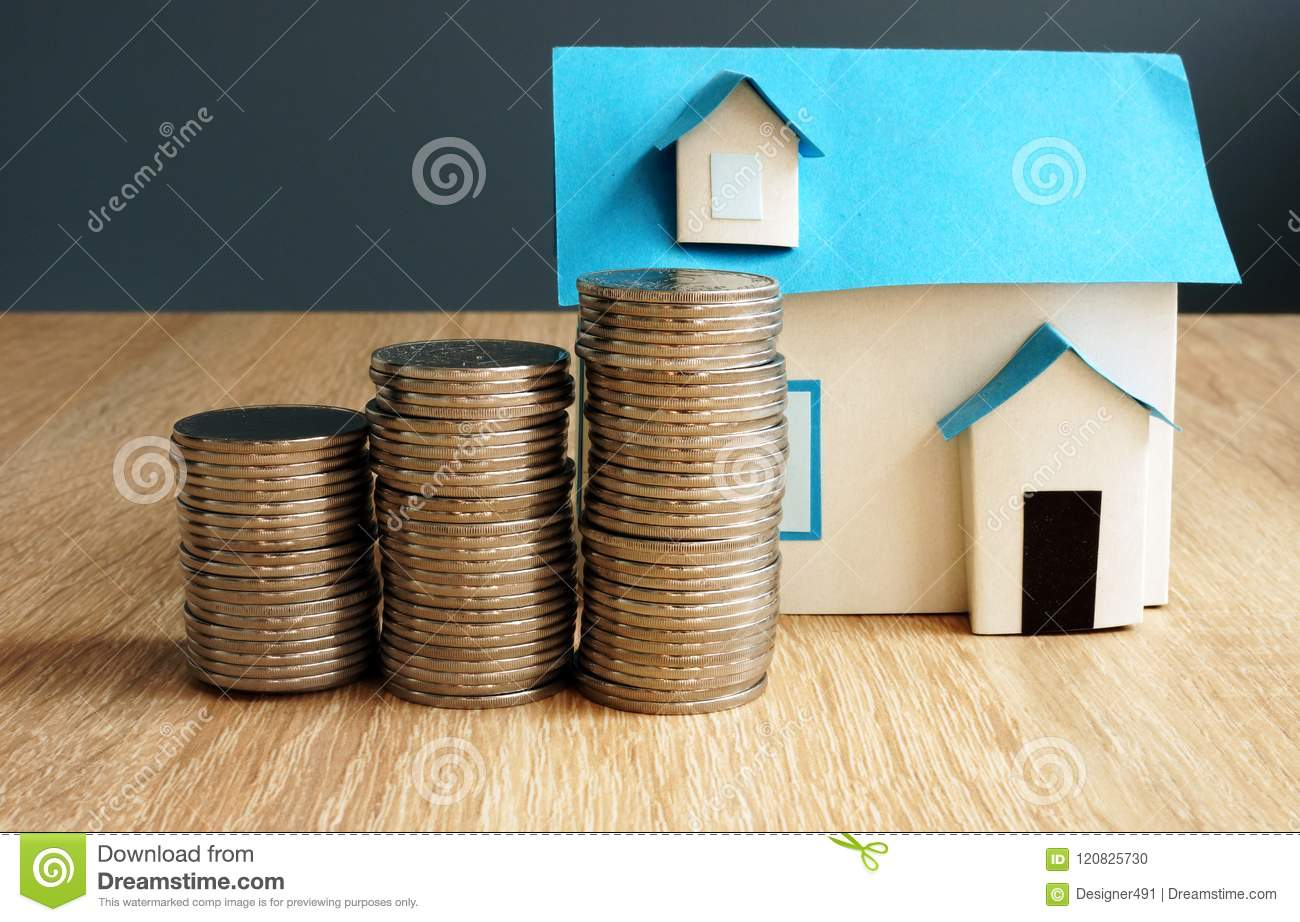 Property value. Model of house and coins.