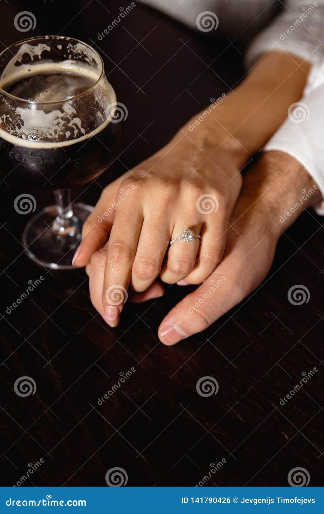 Proposition de vie réelle : Couplez tenir des mains dans un bar avec un verre de bière à leur côté