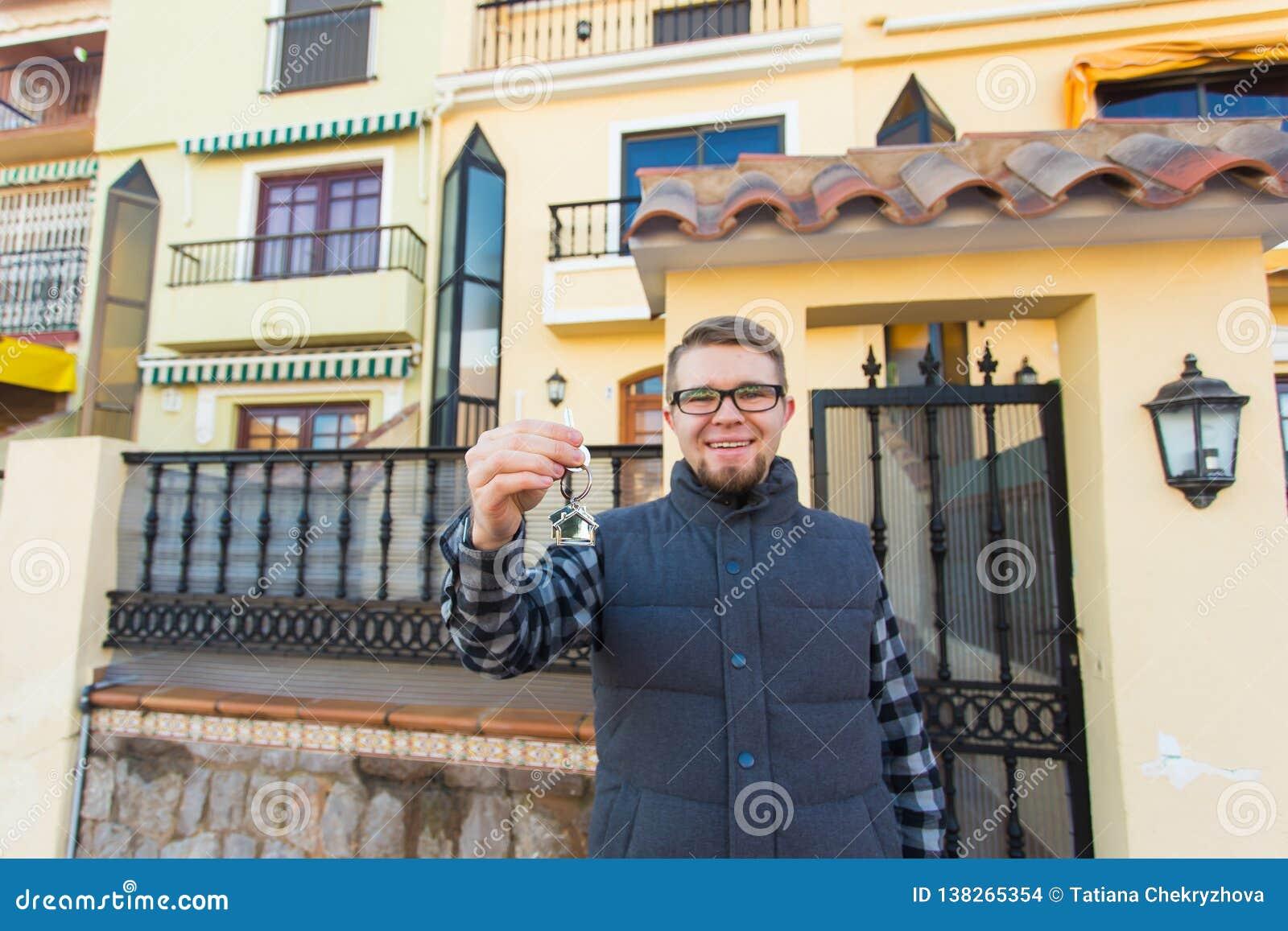 Propriété, propriété, nouvelle maison et concept de personnes - jeune homme avec des clés se tenant en dehors de la nouvelle mais