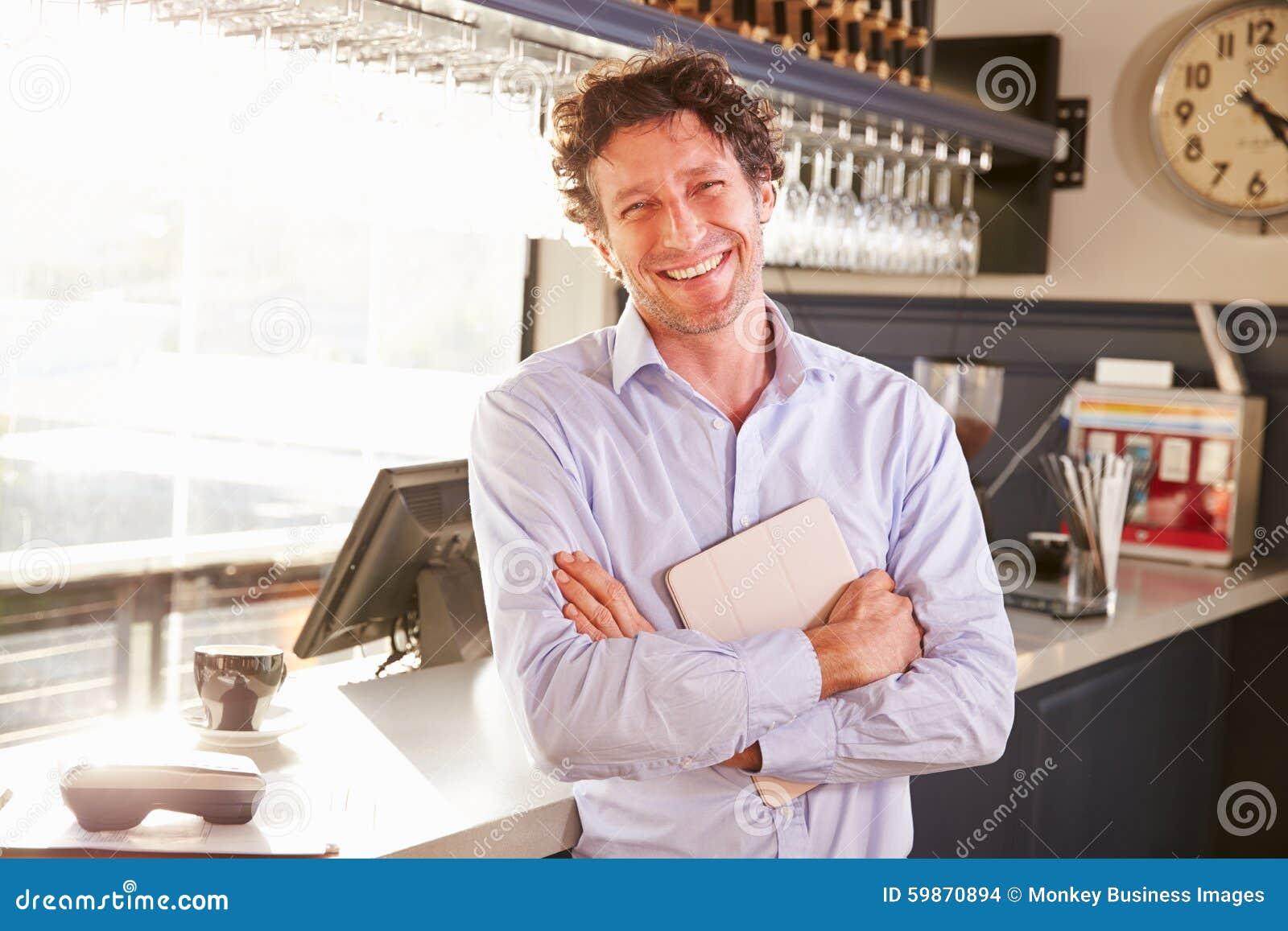 Propriétaire de restaurant masculin tenant le comprimé numérique, portrait