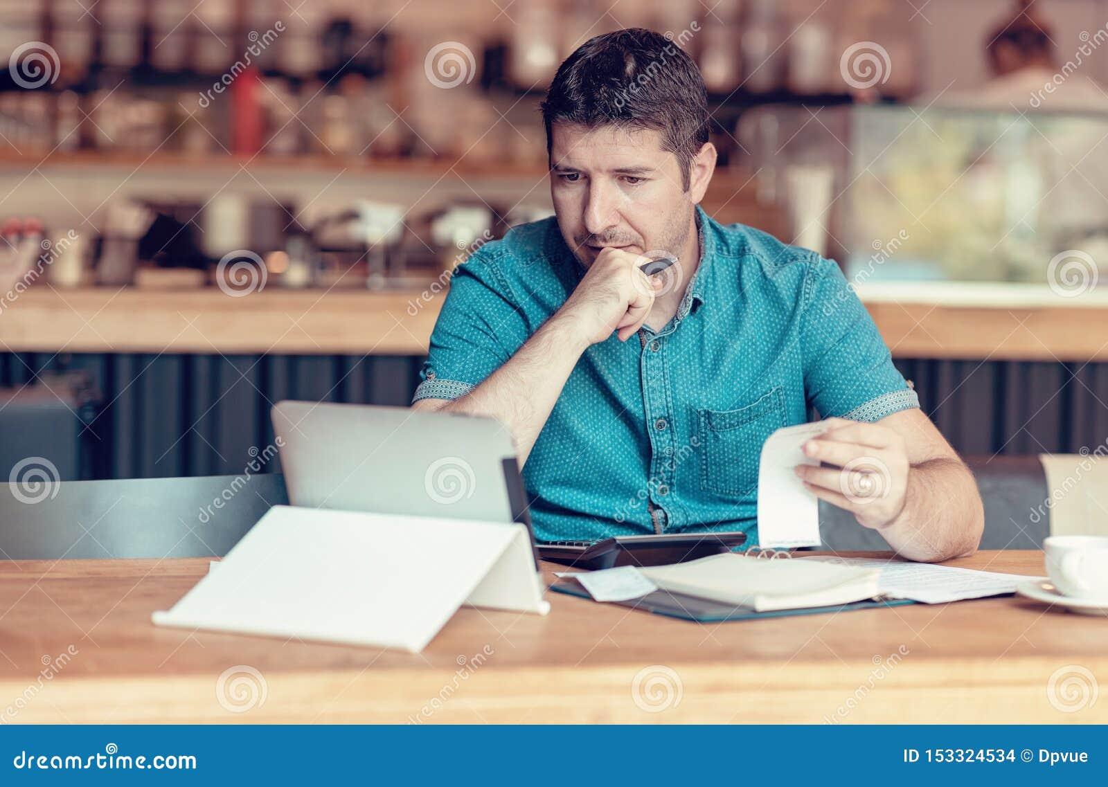 Proprietário de restaurante que verifica relatórios mensais em uma tabuleta, em contas e em despesas de sua empresa de pequeno po