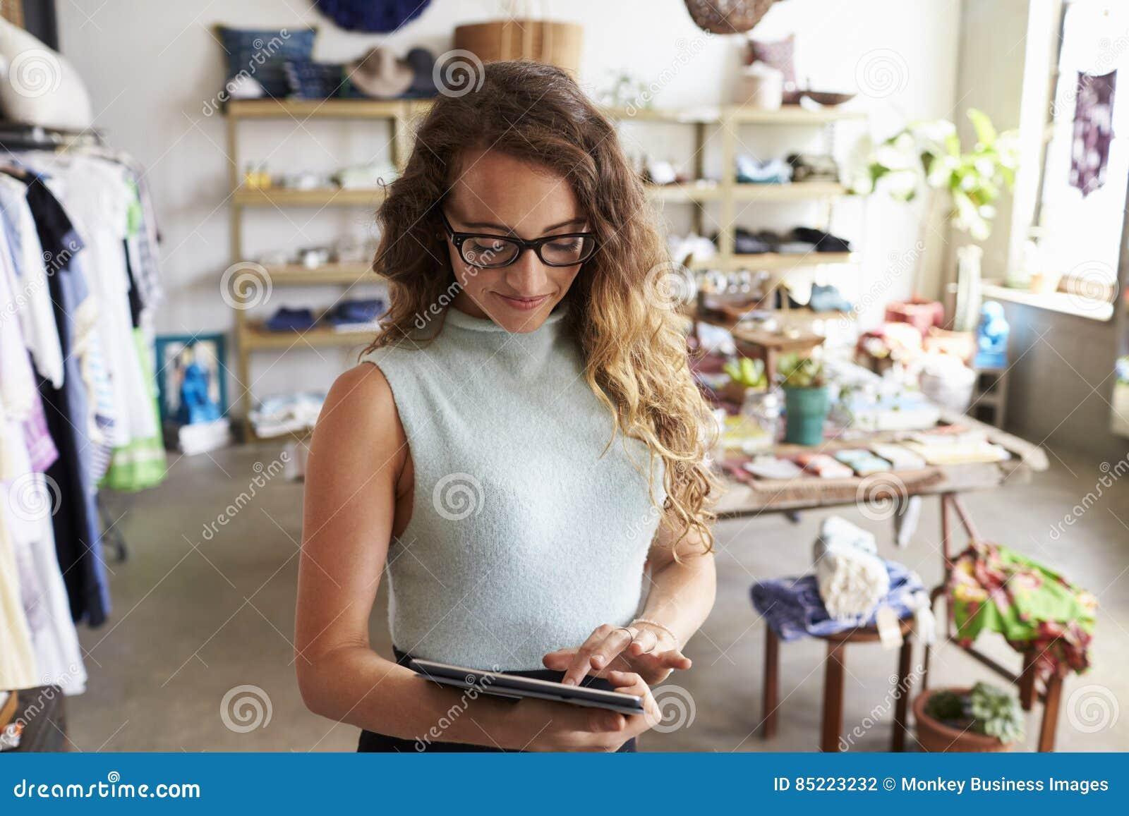 Proprietário empresarial fêmea que usa o tablet pc na loja de roupa
