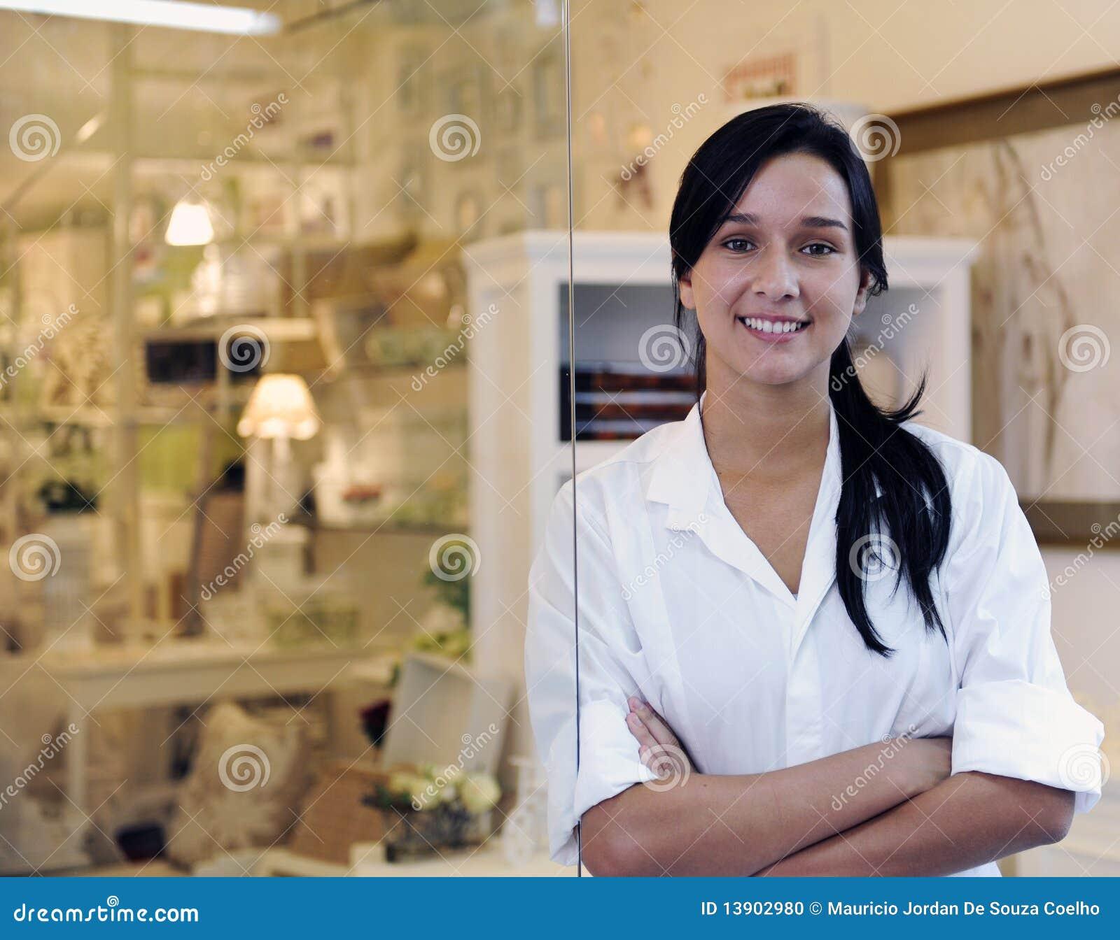 Proprietário empresarial pequeno: mulher orgulhosa e sua loja