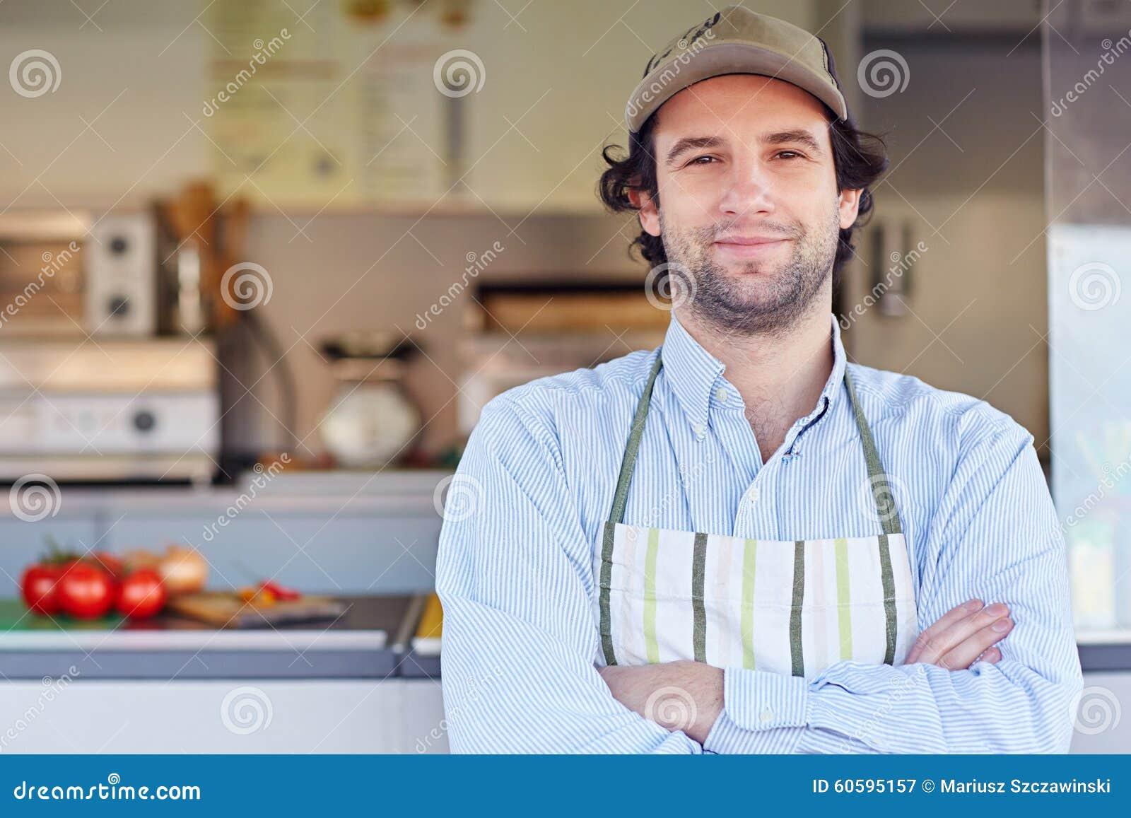 Proprietário empresarial pequeno que sorri na frente de seu busin do alimento afastado