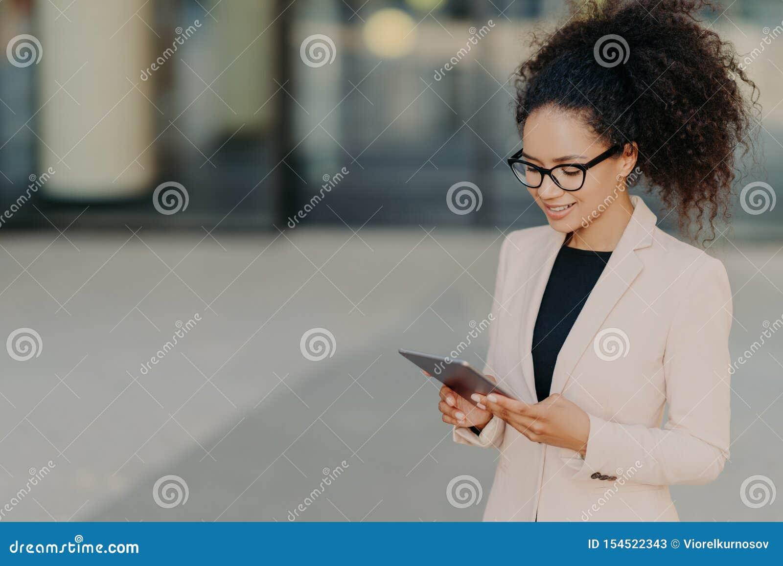 Proprietário próspero de suportes da empresa de negócio com touchpad digital, focalizado na tela, buscas para ideias novas do mer