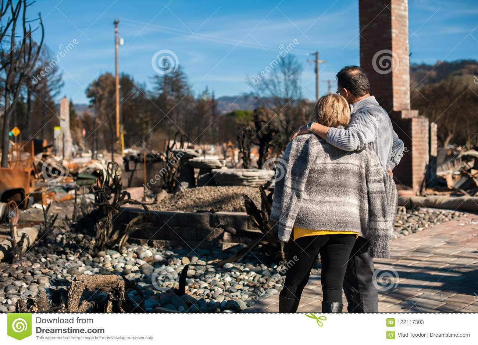 Proprietários, verificando a casa e a jarda queimadas e arruinadas após o fogo