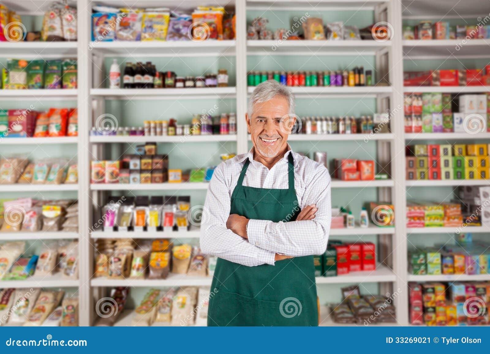 Proprietario maschio senior che sta nel supermercato