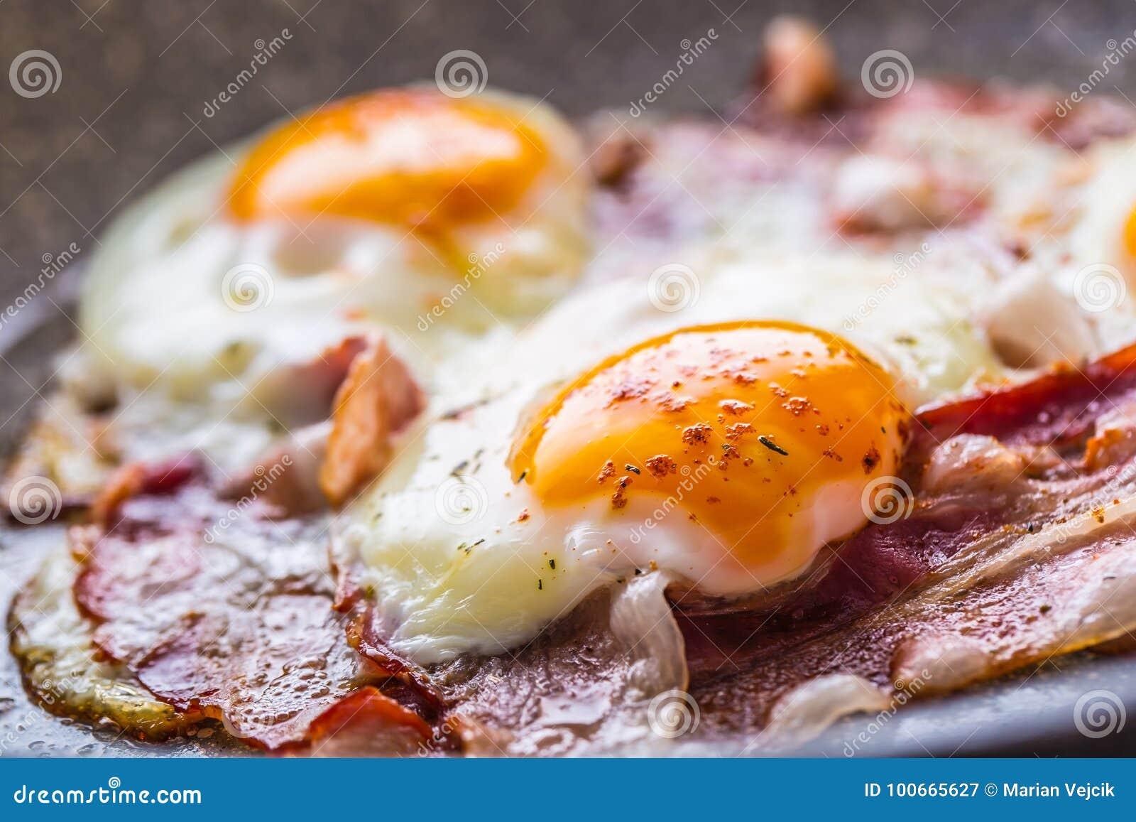 Prosciutto ed uova Bacon ed uova che friggono sulla pentola ceramica Uovo salato e spruzzato con peperone Prima colazione inglese