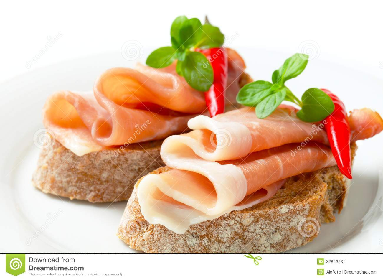 Prosciutto open faced sandwiches garnished with red chili peppers.