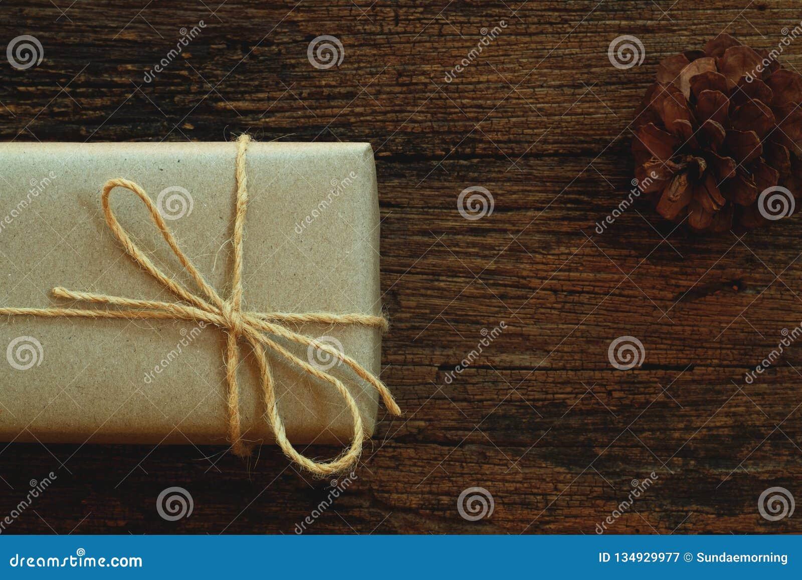 Prostego eco prezenta pudełek pakunku życzliwy opakunek z brązu papierem w starym drewnianym stołowym tle, zieleni teraźniejszy p
