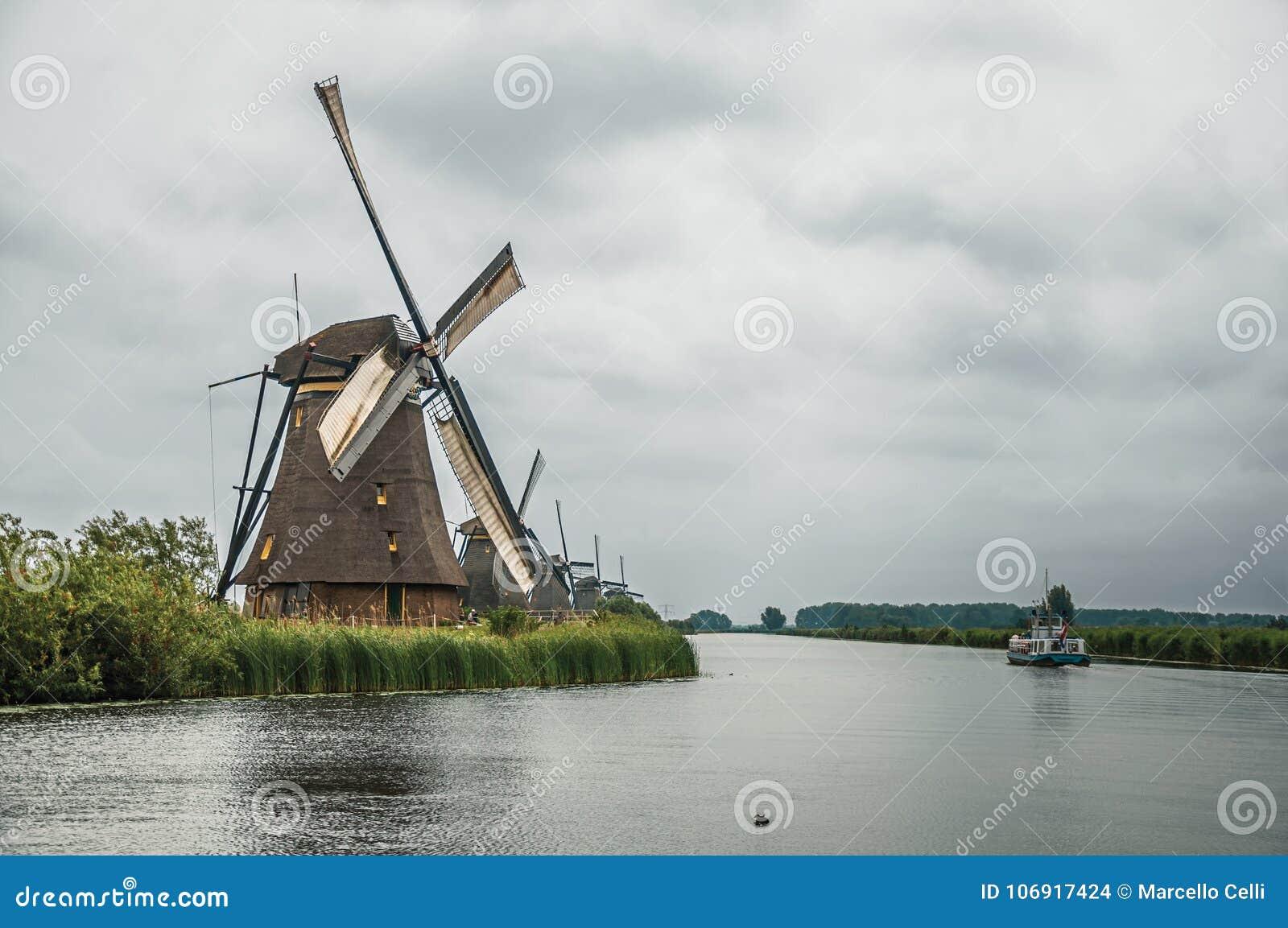 Prosty kanał z wiatraczkami i łodzią w chmurnym dniu przy Kinderdijk