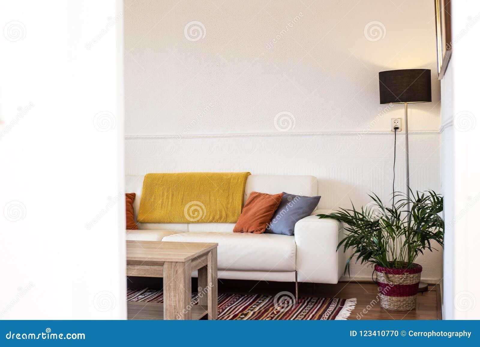 Prosty, przemysłowy wewnętrzny projekt żywy pokój z drewnianą stołową pozycją przed szarą kanapą z poduszkami,
