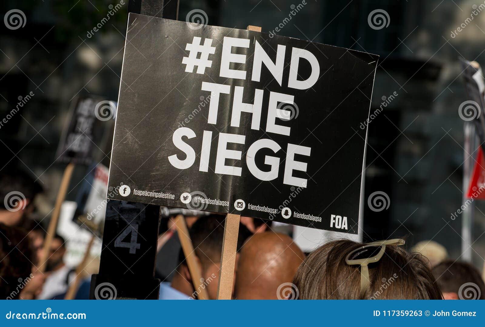 Protesteerder met aanplakbiljet in Gaza: Houd de Slachtingsverzameling in Whitehall, Londen, het UK tegen