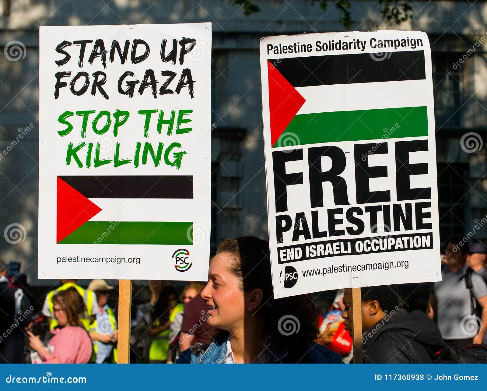 Protesteerders met aanplakbiljetten in Gaza: Houd de Slachtingsverzameling in Whitehall, Londen, het UK tegen