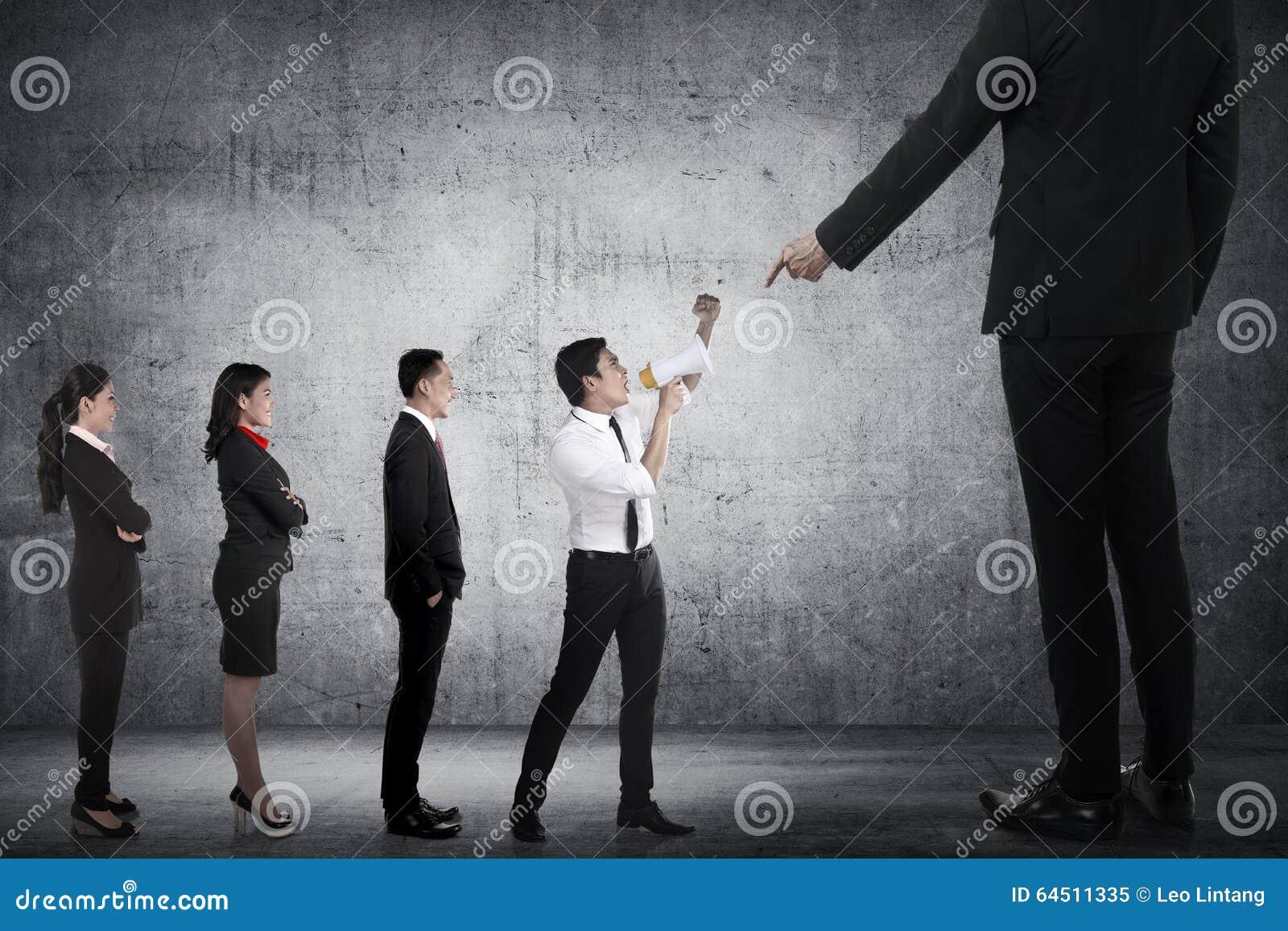Protesto da equipe do negócio ao chefe que usa o megafone