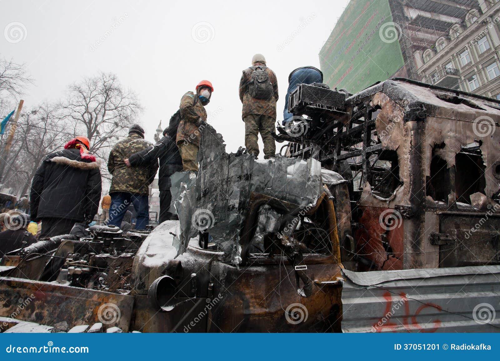 Protestujący z chowanym twarz strażnikiem na wierzchołku palący i roztrzaskujący autobusy na zimy ulicie podczas antyrządowego pro